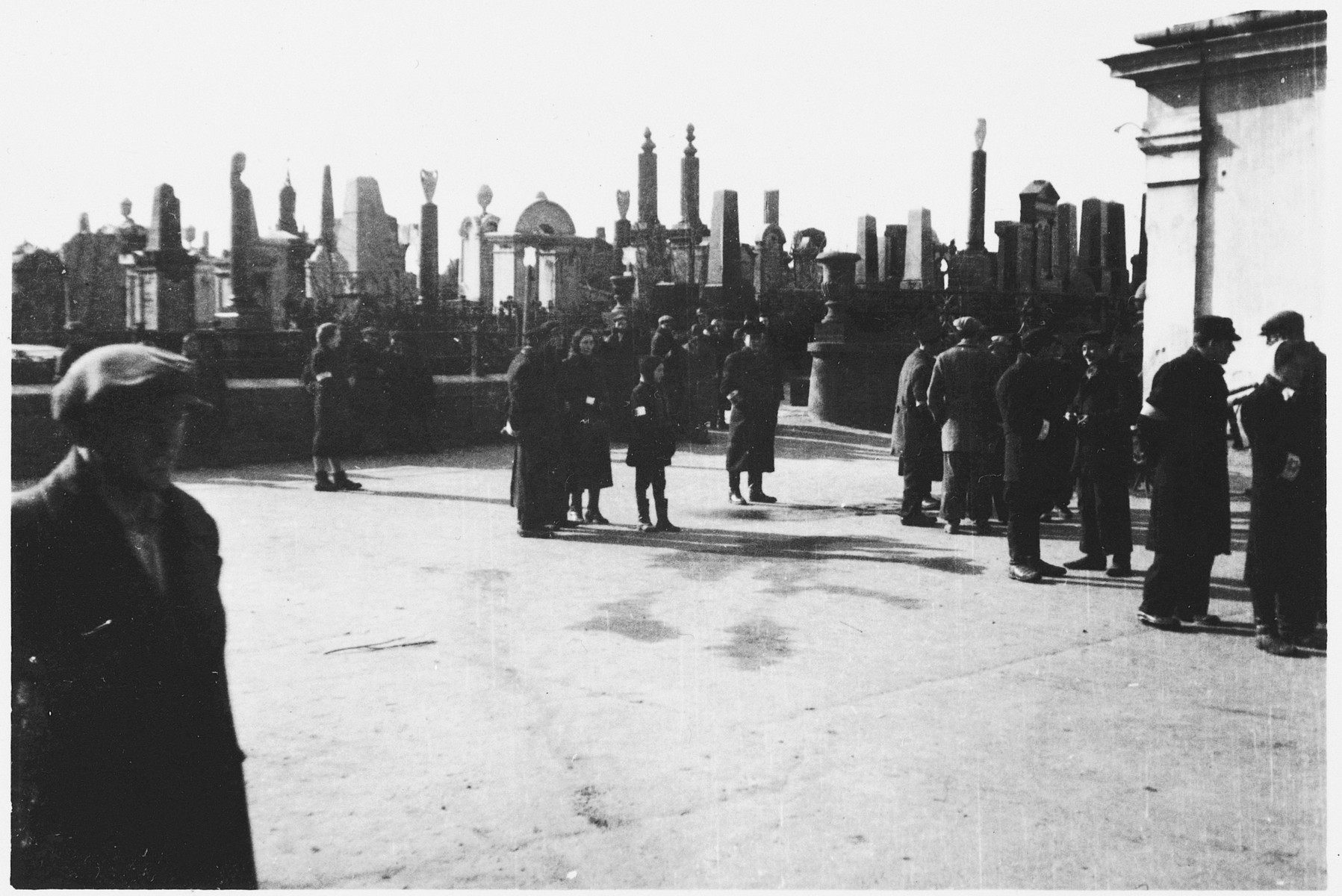 Jews from the Warsaw ghetto congregate at the entrance to the cemetery.