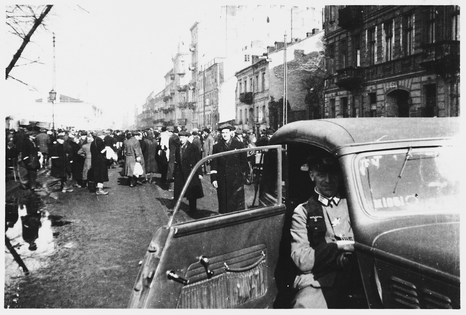 A German officer views the scene on a crowded street in the Warsaw ghetto from the open door of his automobile.