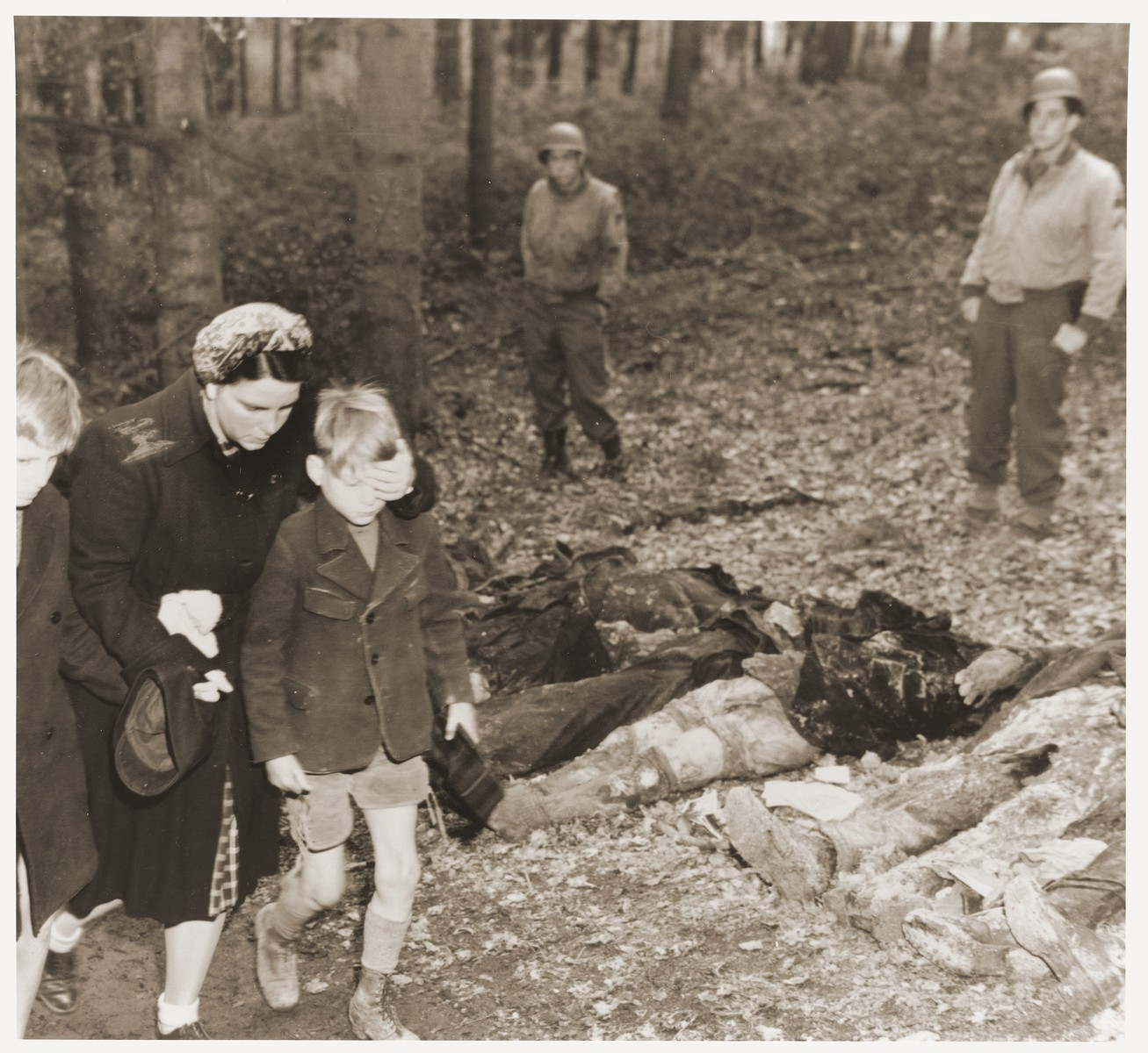 Under the supervision of American soldiers, a German mother shields the eyes of her son as she walks with other civilians past the bodies of 57 Russians, including women and one baby, exhumed from a mass grave outside the town of Suttrop.    The victims were forced to dig their own grave and then were shot by SS troops six weeks before the arrival of American troops.  On May 3, 1945, the 95th Infantry Division of the U.S. Ninth Army arrived in Suttrop and were informed by locals of the mass grave.  American troops forced the townspeople to exhume the grave after which Russian displaced persons in the area identified the bodies.  The victims were reburied in individual graves, and a U.S. Army chaplain conducted burial services.  Russians remaining in the area placed wreaths on the graves.