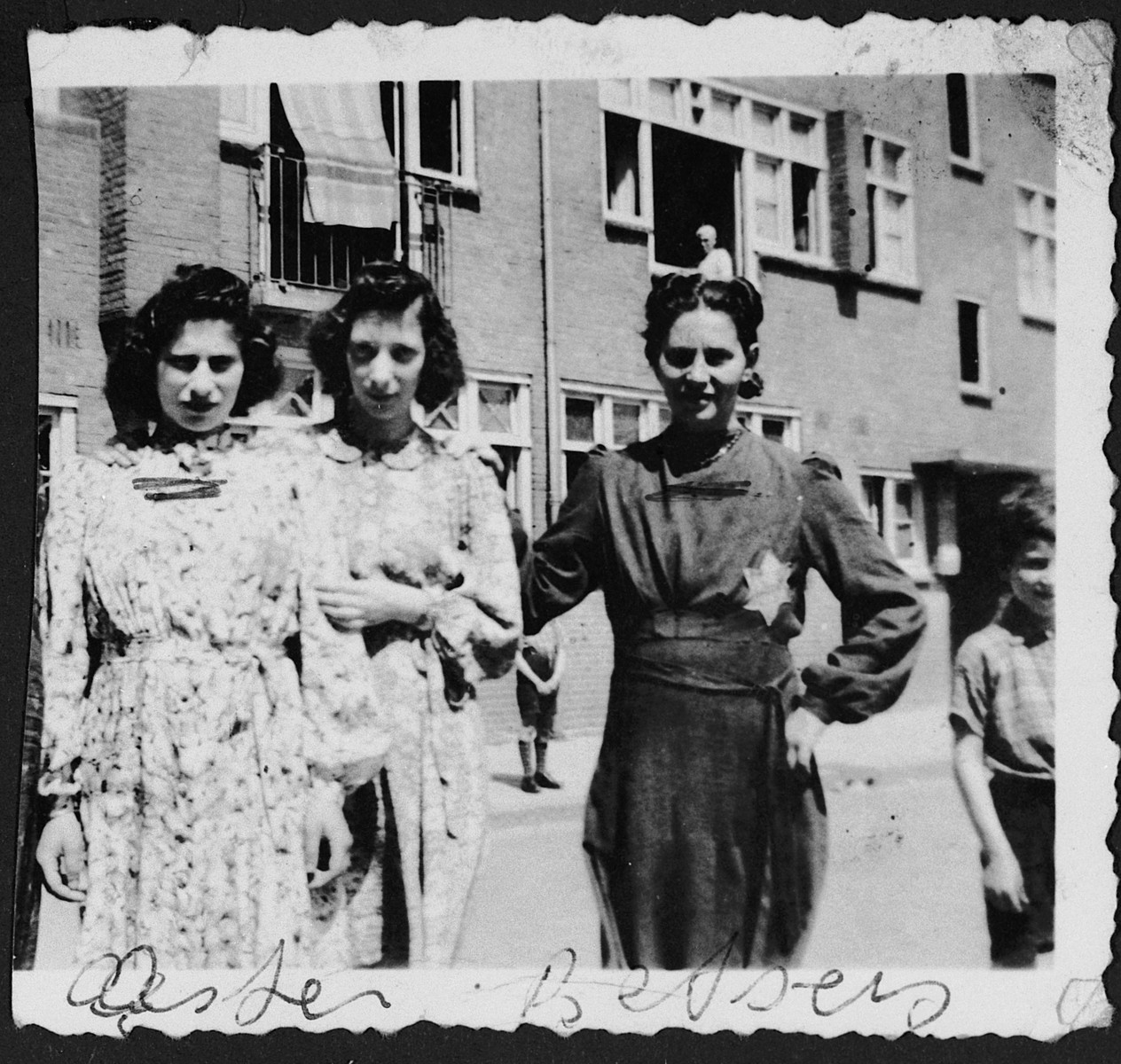 Three young women, one of whom is wearing a star, stand on a street corner.  From left to right are Ester Swaab Franshman, unknown and Betsy Visser Swaab.