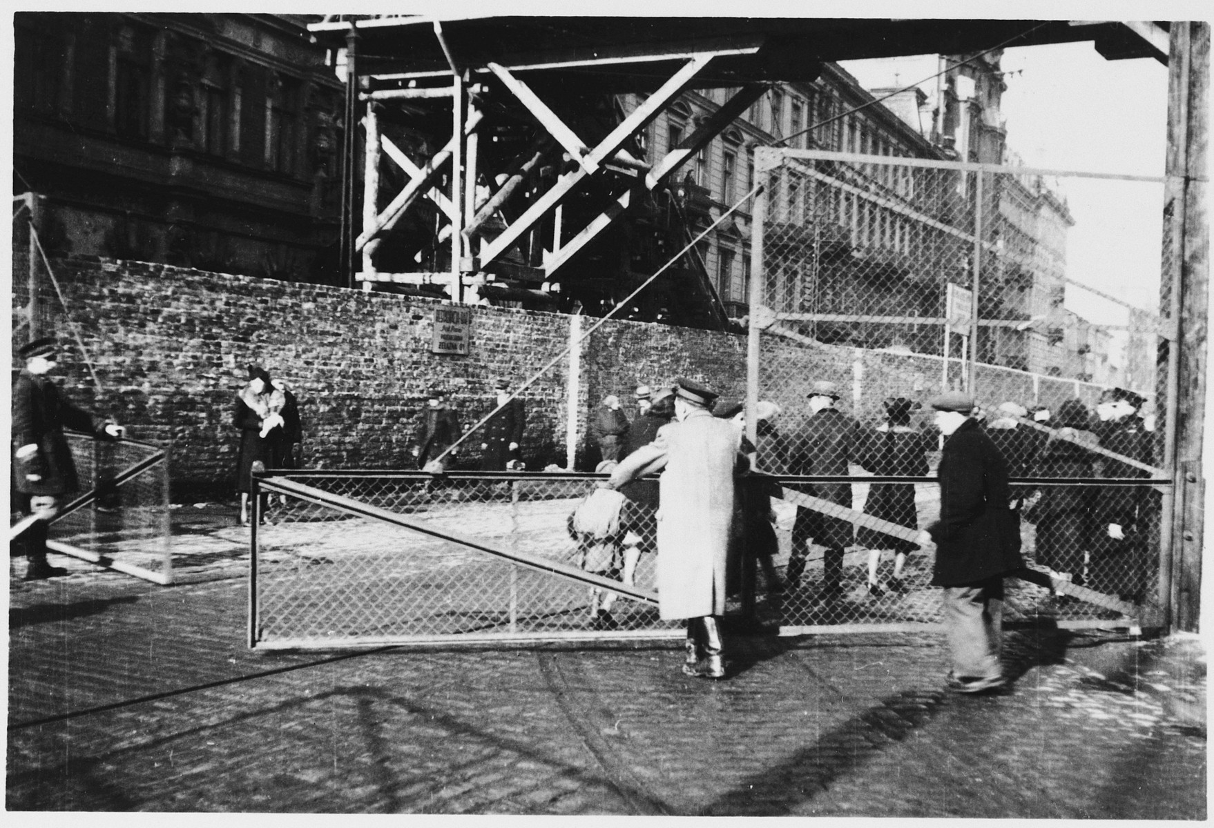 Jewish police open the gates to a street that divides the Warsaw ghetto.  Above a pedestrian bridge spans the two sections of the ghetto.