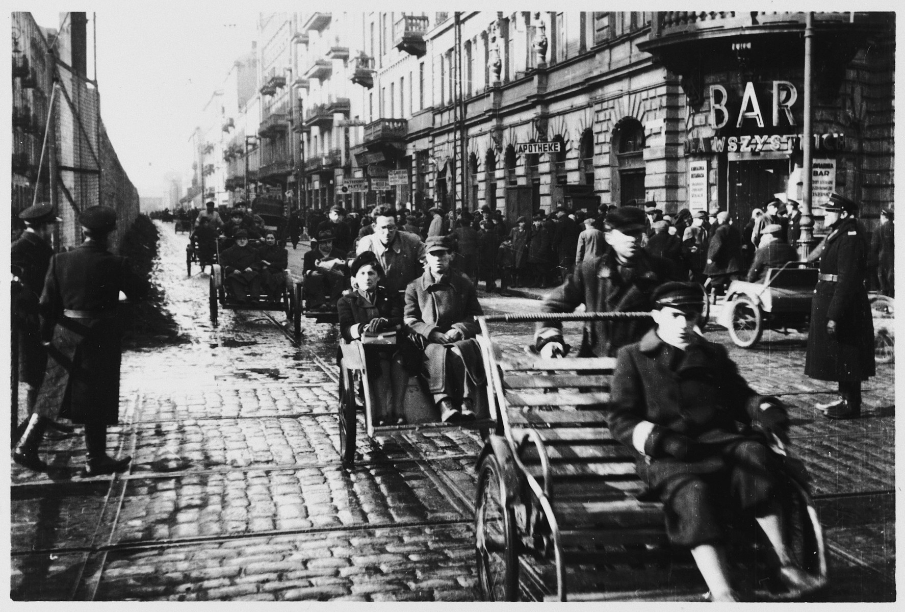 Bicycle-powered rickshaws transport Jews down a crowded street in the Warsaw ghetto.