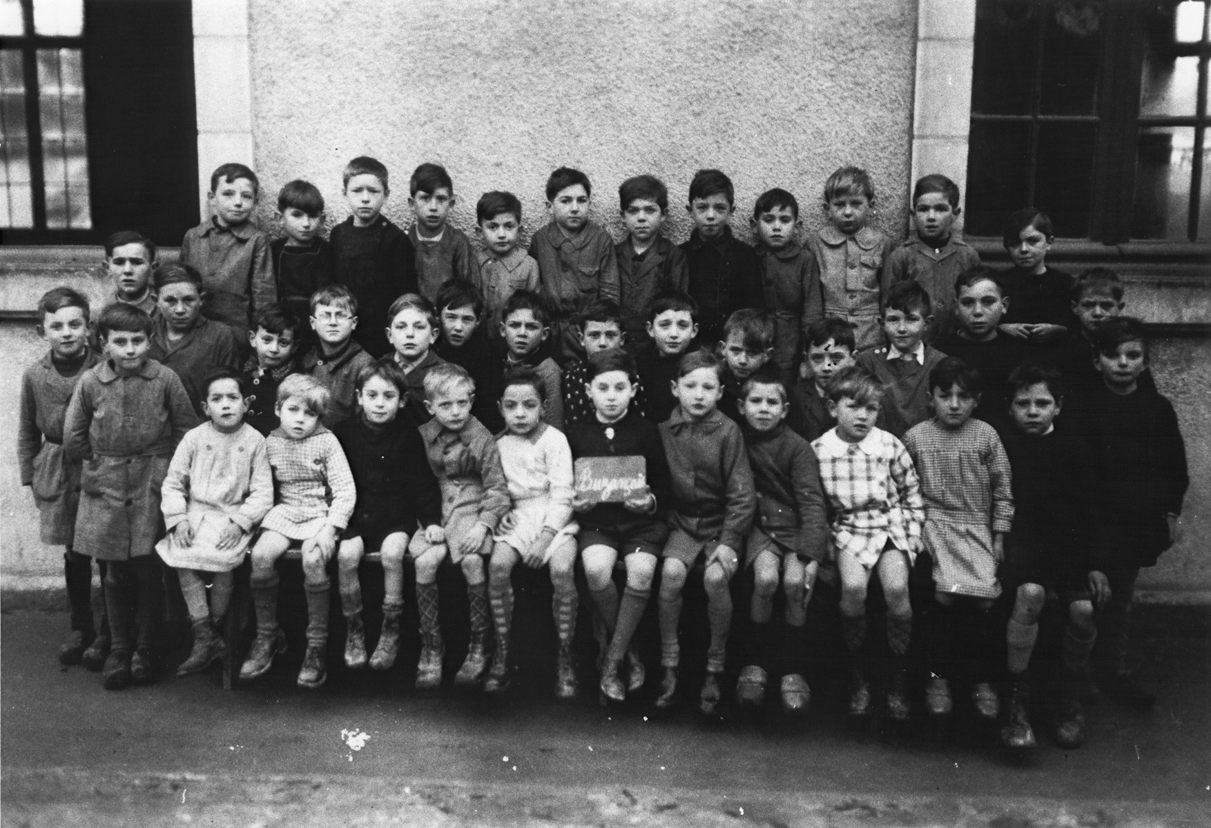 Group portrait of an elementary school class in Buzancais, France that included a Jewish child in hiding.  Herbert Odenheimer is pictured in the front row holding a sign with the name of the town.