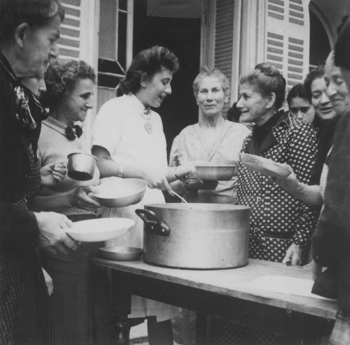 OSE relief worker Margot Stein serves soup to a group of Jewish refugee women at the Hotel Bompard internment camp.