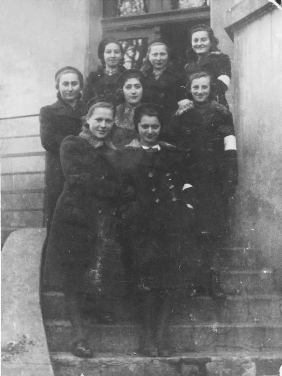 A group of Jewish teenage girls wearing armbands pose on the stairs outside a building in Bedzin.  Among those pictured is Chana Szlezyngier (front row center) and Tosia Szwajcer, the only one of the group to survive.