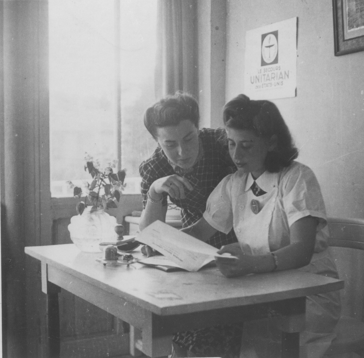 Margot Stein and Mrs. Zimmer, the wife of a physician of the Unitarian Service Committee, examine a document in their office at the Hotel Bompard internment camp.