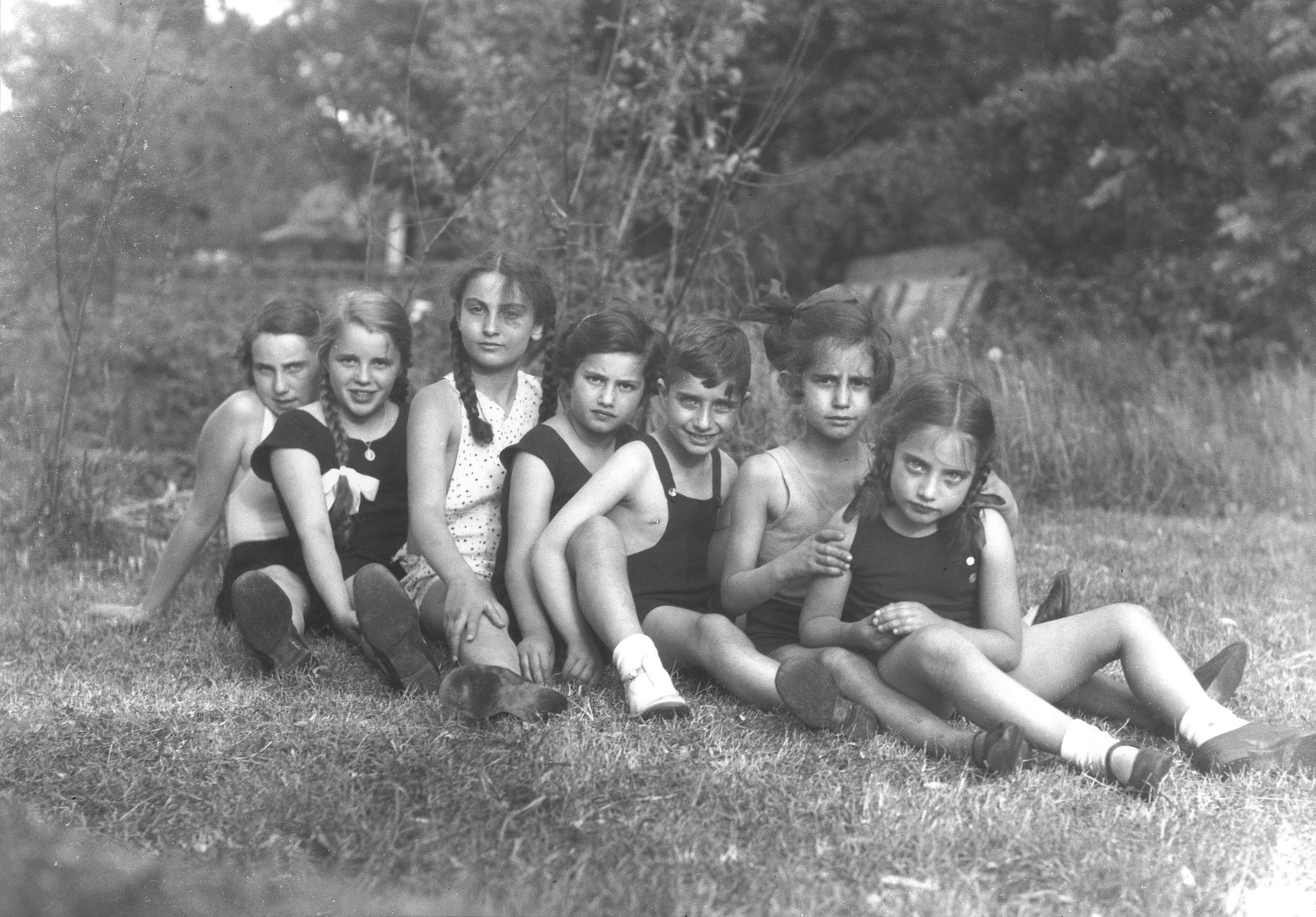 The children of Georg and Gertrude Anker sit in a row on the grass with their friends and cousins.  Pictured are Eva, Dodi and Hilde Anker, their cousins Heinz and Else Karplus, and two friends.