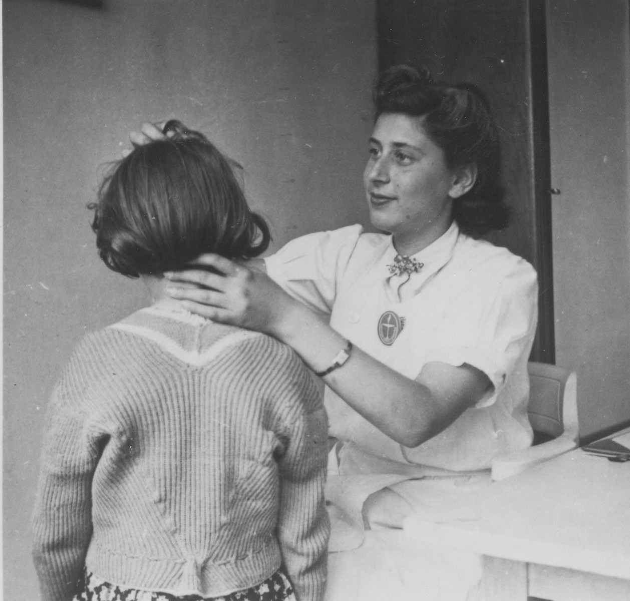 OSE relief worker Margot Stein gives a medical examination to a child at the Hotel Bompard internment camp.