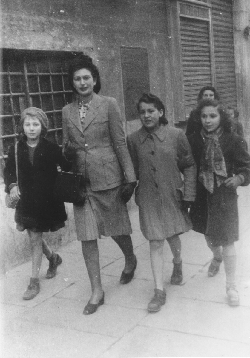 Hanna Rawicz walks along a street in Rome with friends during the period before she went into hiding in a convent.  Among those pictured are Hanna Rawicz (first from the right); Sonja Salem (second from the right); and Anna Ehrenberg (first from the left).