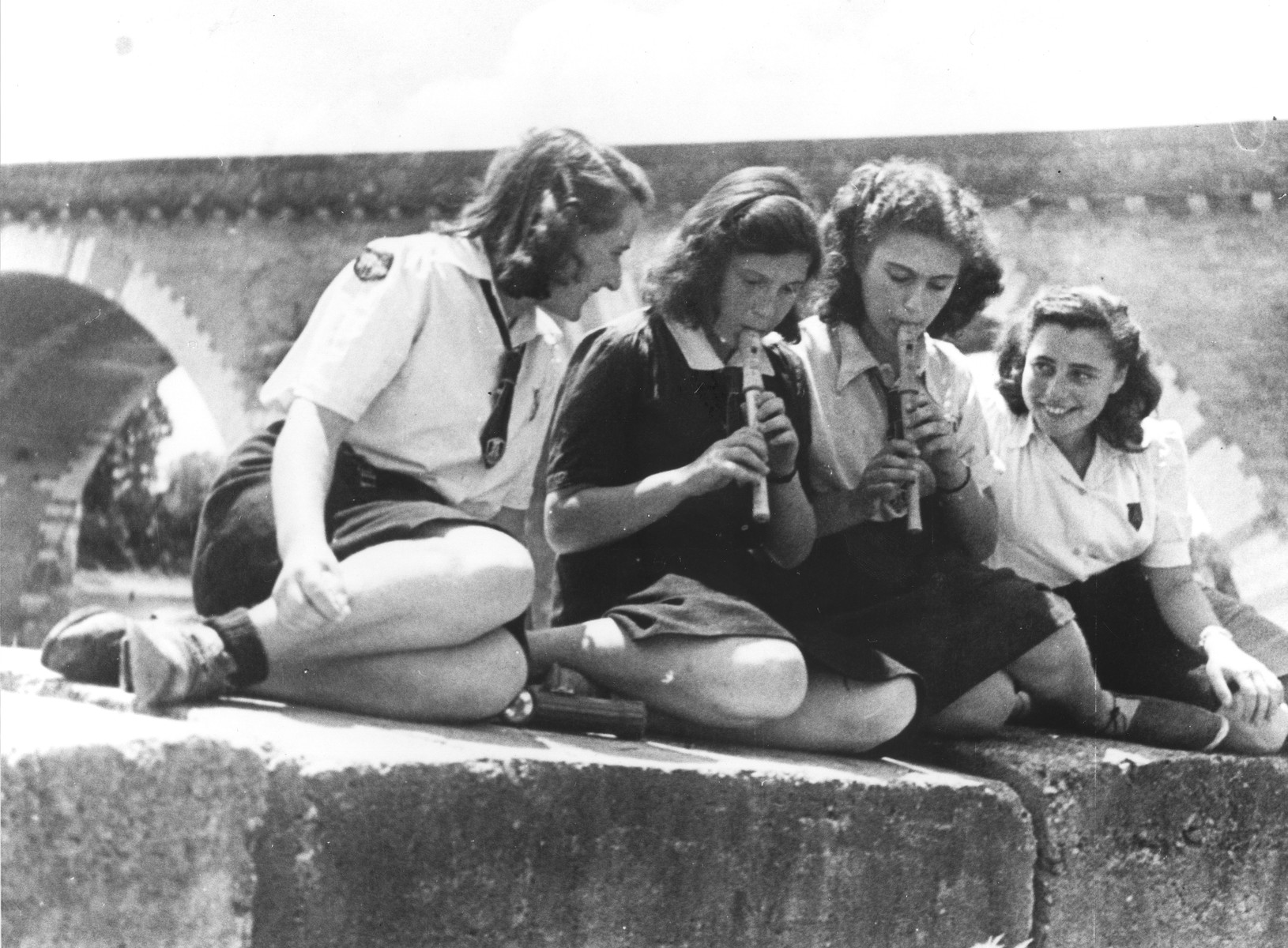 A group of Jewish girl scouts living at the Moissac children's home, play recorders on a riverbank.    Pictured on the far right is Edith Loeb.  On the far left is Trudy Elkan Kuhn.