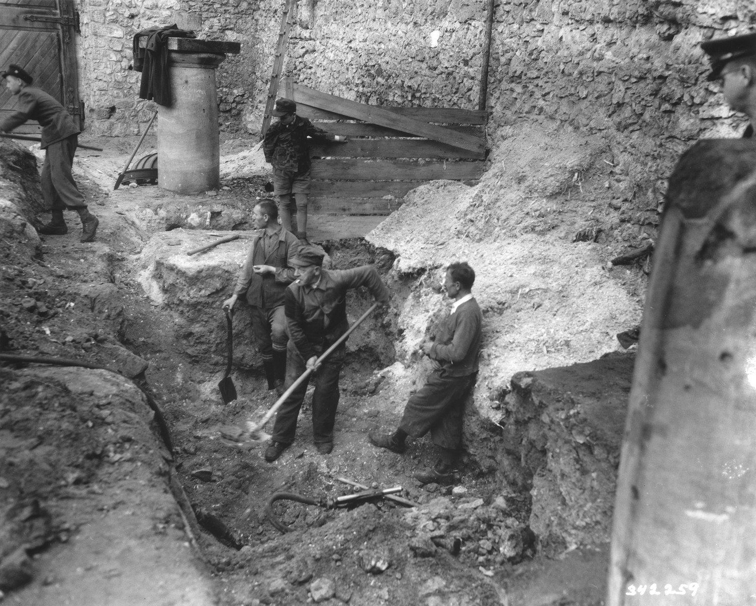 German laborers dig in the courtyard of the Veldenstein castle, formerly owned by Hermann Goering, in search of property looted by the Nazi regime.