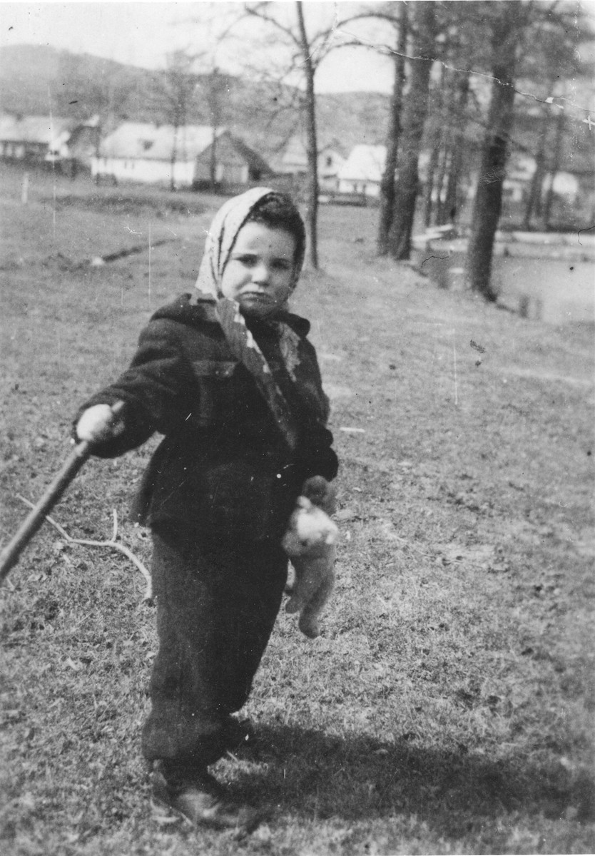 Zdenka Husserlova, a three-year-old Czech Jewish child, stands in an open field clutching her teddy bear.  The photo was taken shortly before her deportation to Theresienstadt.