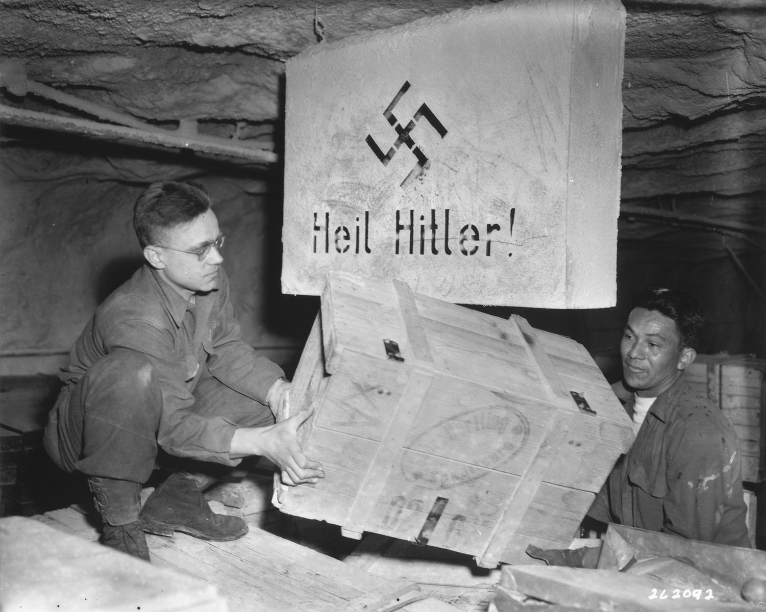 "Two soldiers of the 90th Division, U.S. Third Army, remove a crate containing looted historical engravings that were discovered in the Merkers salt mine.  Above them is a slab with the words ""Heil Hitler"" written on it."