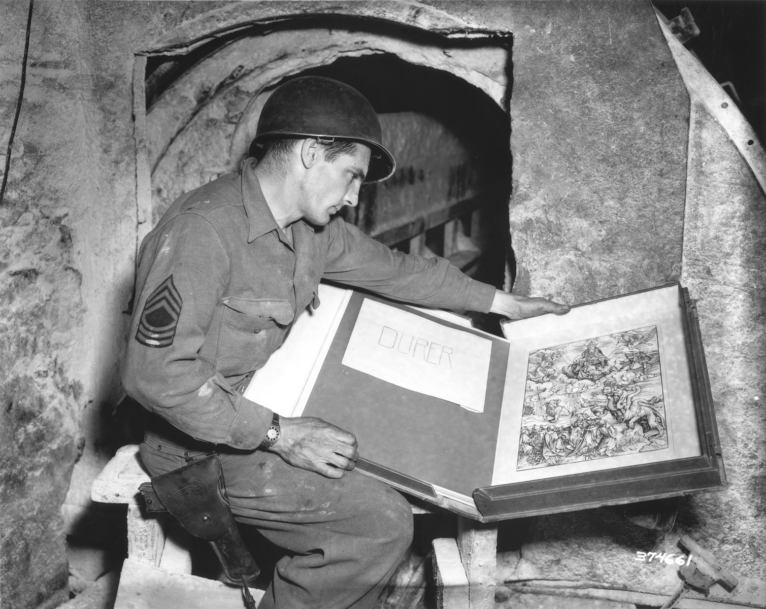 Sgt. Harold Maus of Scranton, PA examines an album of engravings by Albrecht Duerer that was found in a vault containing numerous other art treasures that were looted by the Nazi regime.