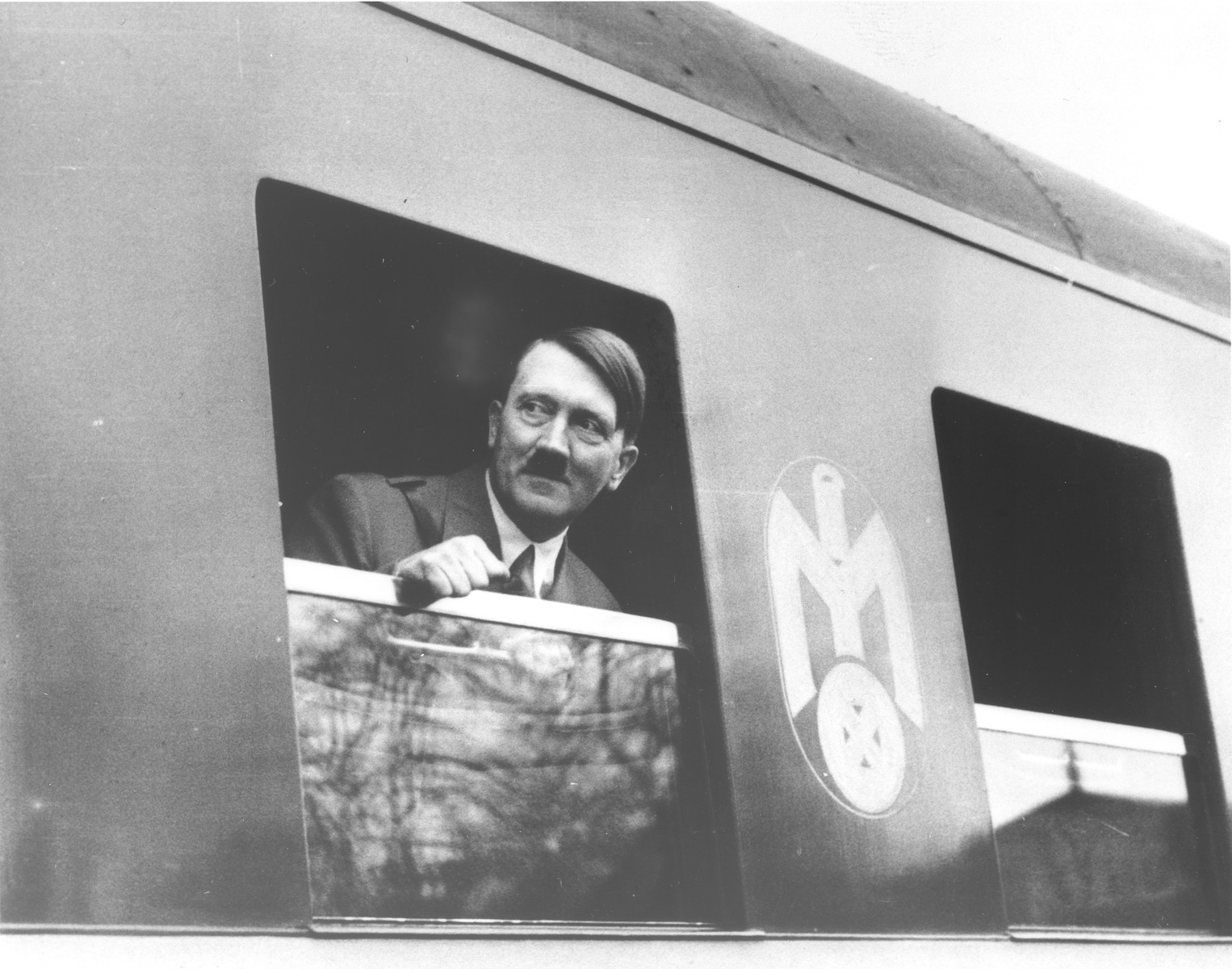 Adolf Hitler looks out the window of a train.