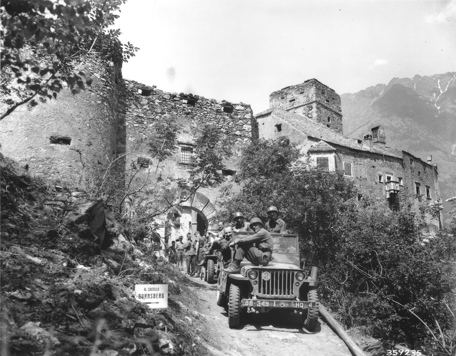 Officers of the Fifth U.S. Army prepare to leave Dornsberg castle after having found large quantities of silk, wool and other goods looted by the Nazis.  Doctor van Hartner, an alleged representative of the International Red Cross from Budapest who is guiding the Americans to places where looted items have been hidden, is seated in the first jeep.
