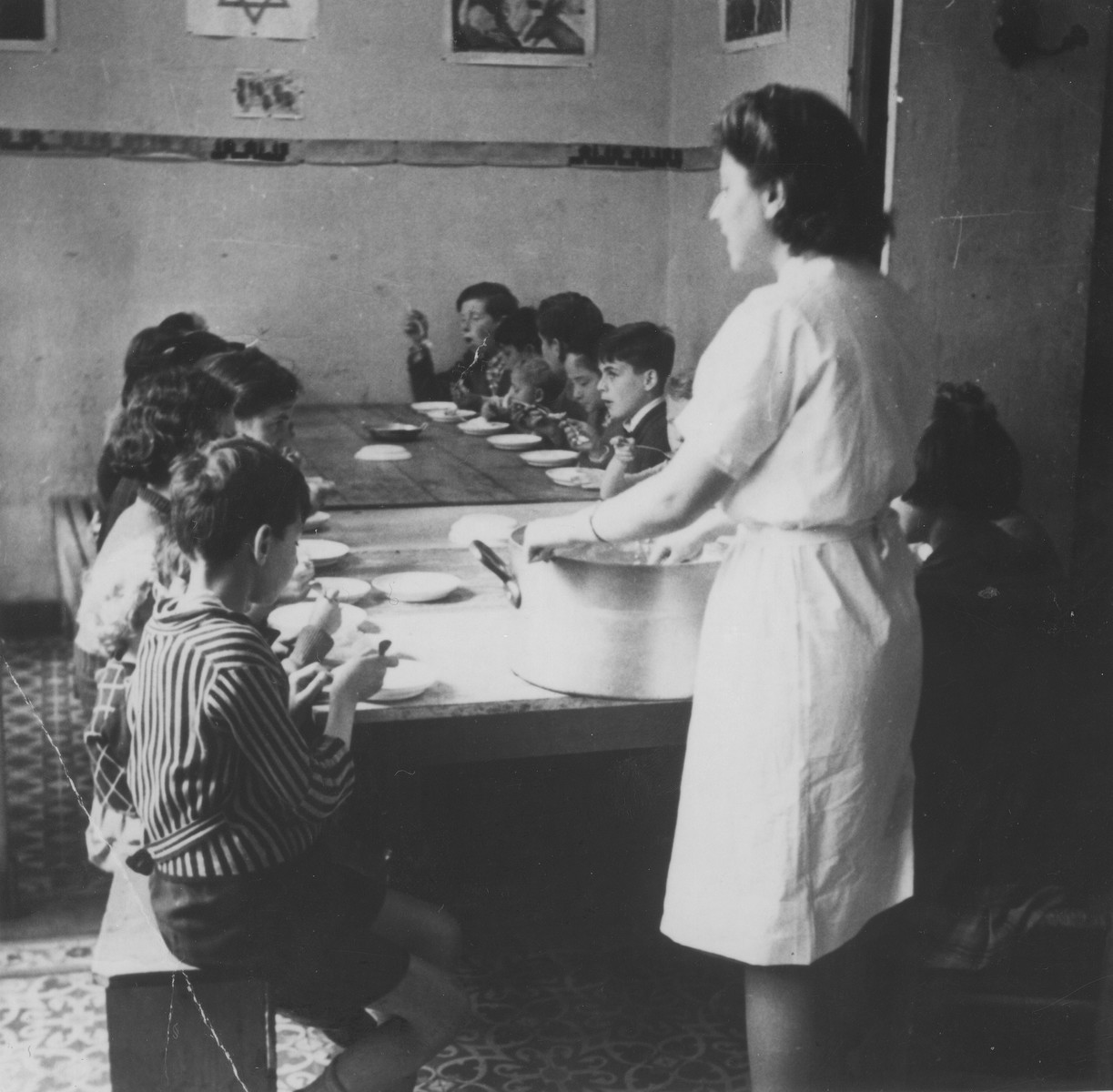 OSE relief worker Margot Stein serves soup to children at the Hotel Bompard internment camp.
