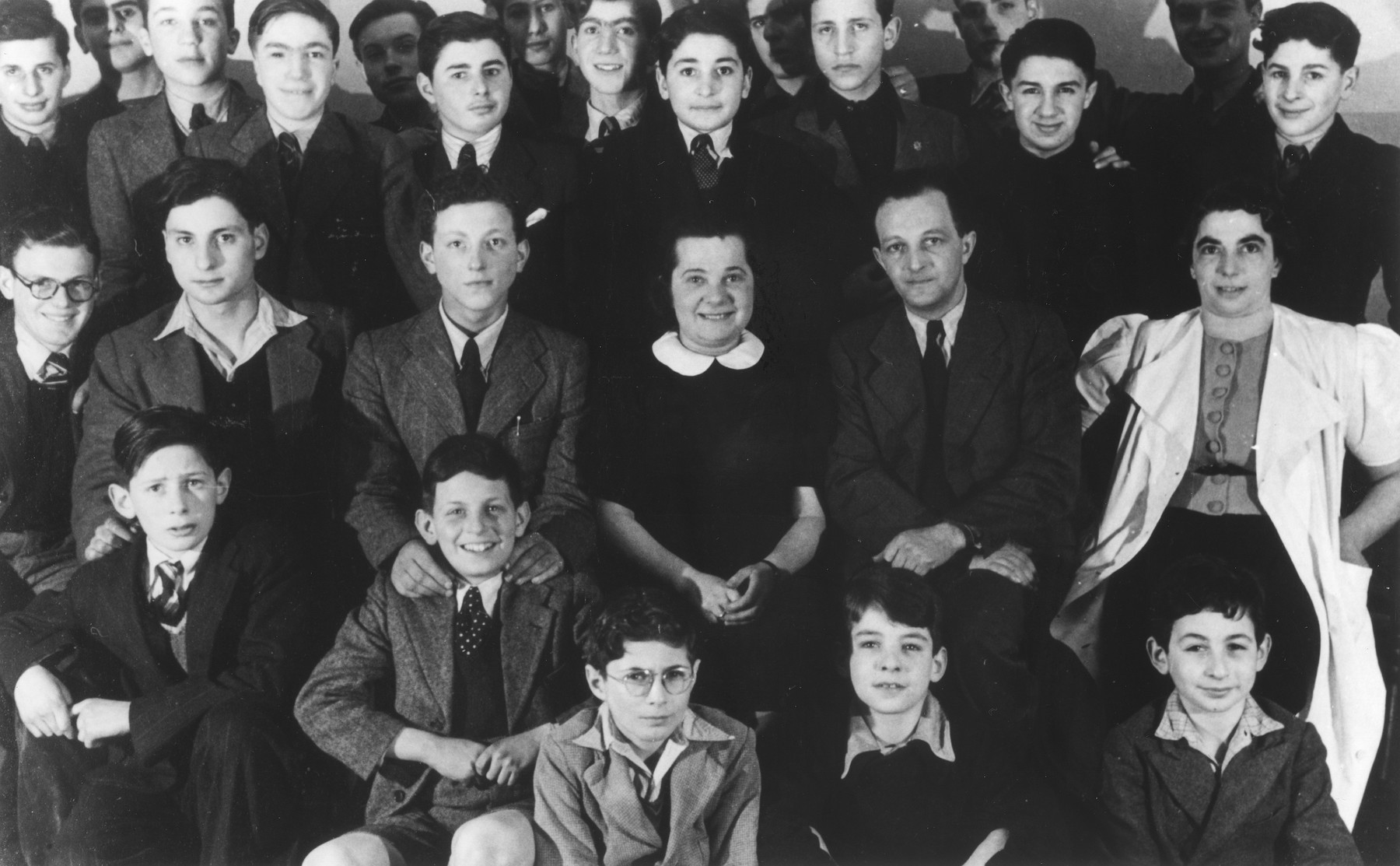 Group portrait of German Jewish refugee children and their caretakers who came to England from the Netherlands.  Among those pictured are Mr. Siegfried Alexander and his wife Erna and the housemother, Martha Strauss (in the white coat).