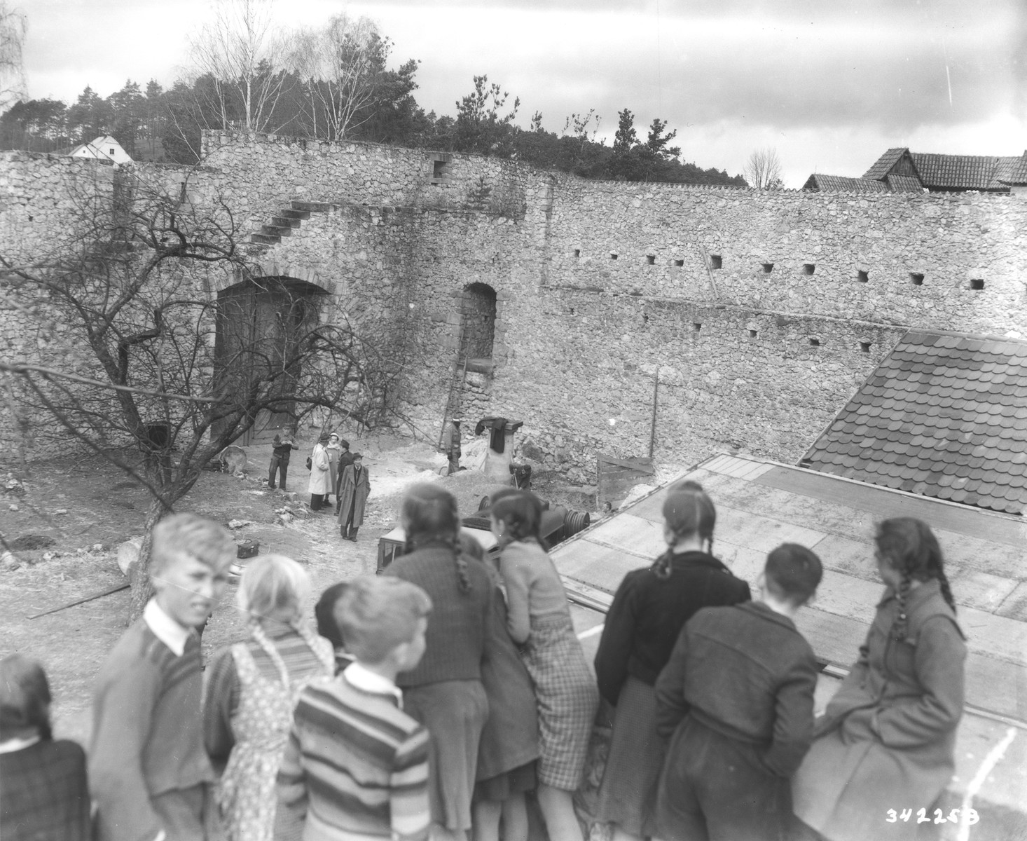 Displaced children who are being housed in Veldenstein castle, formerly owned by Hermann Goering, watch as German workers search for property looted by the Nazi regime.