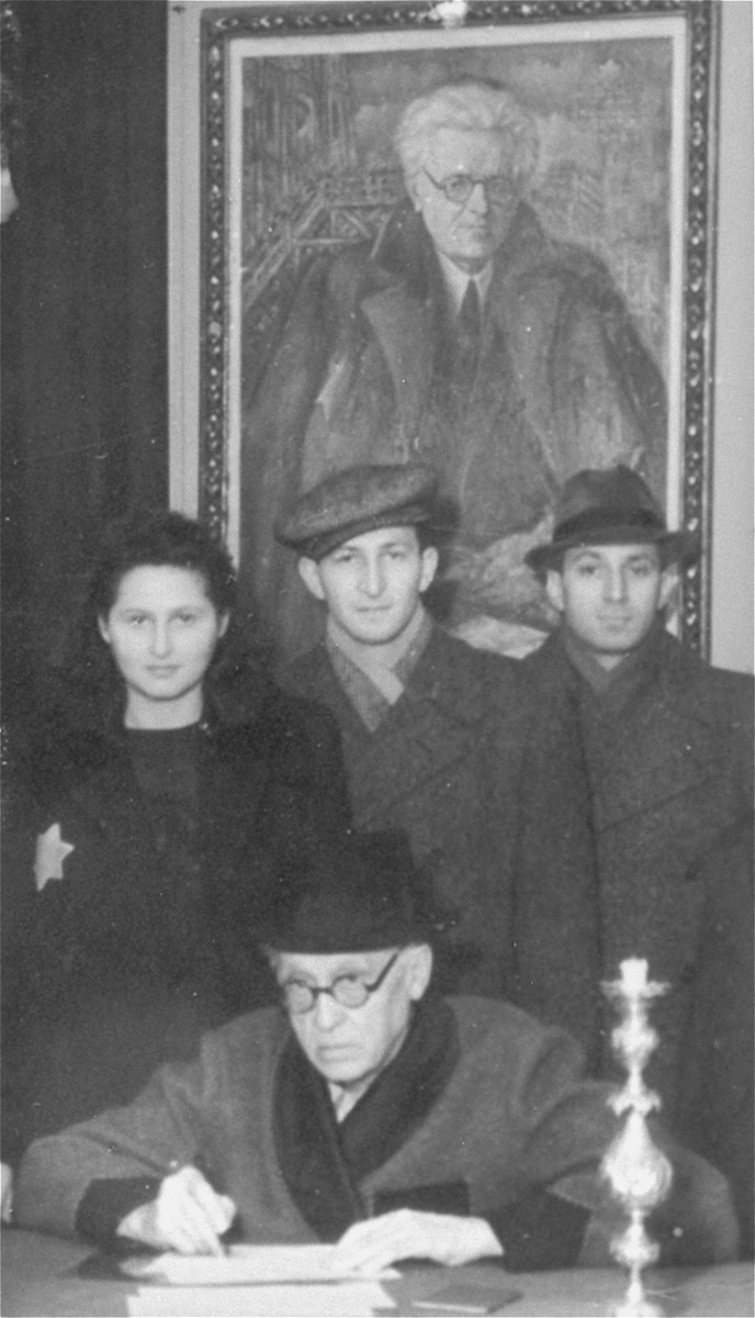 Lodz ghetto Jewish council chairman Mordechai Chaim Rumkowski officiates at the wedding of Nachman Zonabend and Irka Kuperminc.     The group poses in front of a painting of Rumkowski.  Pictured standing from the left are:  Irka Kuperminc, Nachman Zonabend, and Nachman's brother Isak.  Seated is Mordechai Chaim Rumkowski.