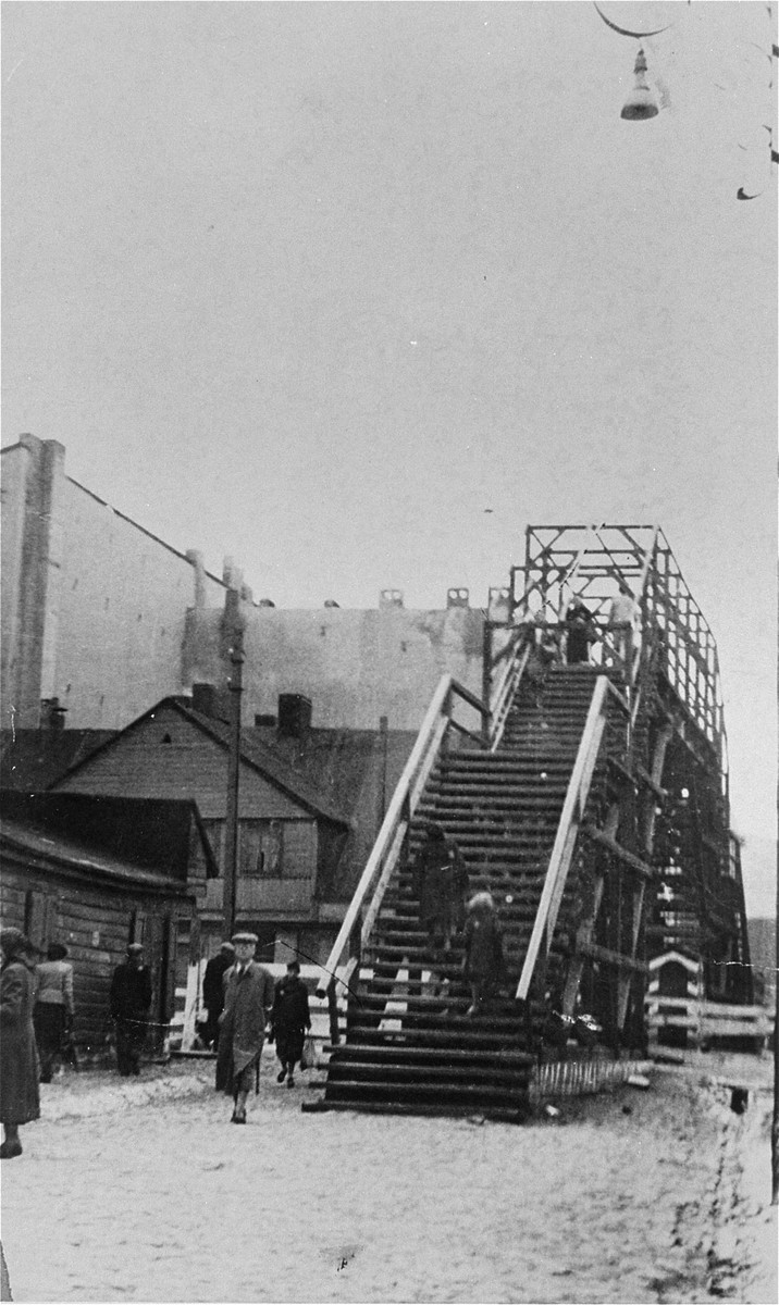 "View of Lodz ghetto residents climbing the staircase to cross one of the pedestrian bridges.  The Yiddish inscription on the back of the photo reads, ""The ghetto through the bridge on Marynarska Street via Aleksandrov Street - Fayfer's Alley."""