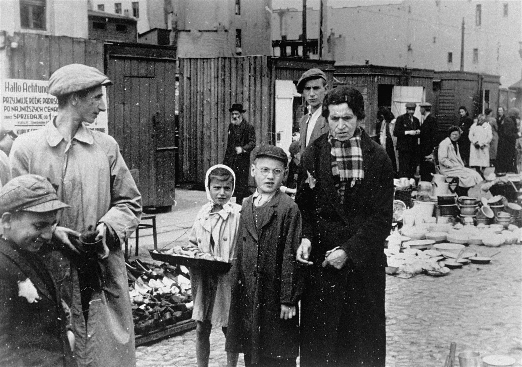 People at the outdoor market in the Lodz ghetto.  A child vendor carries her wares in a tray slung around her neck.