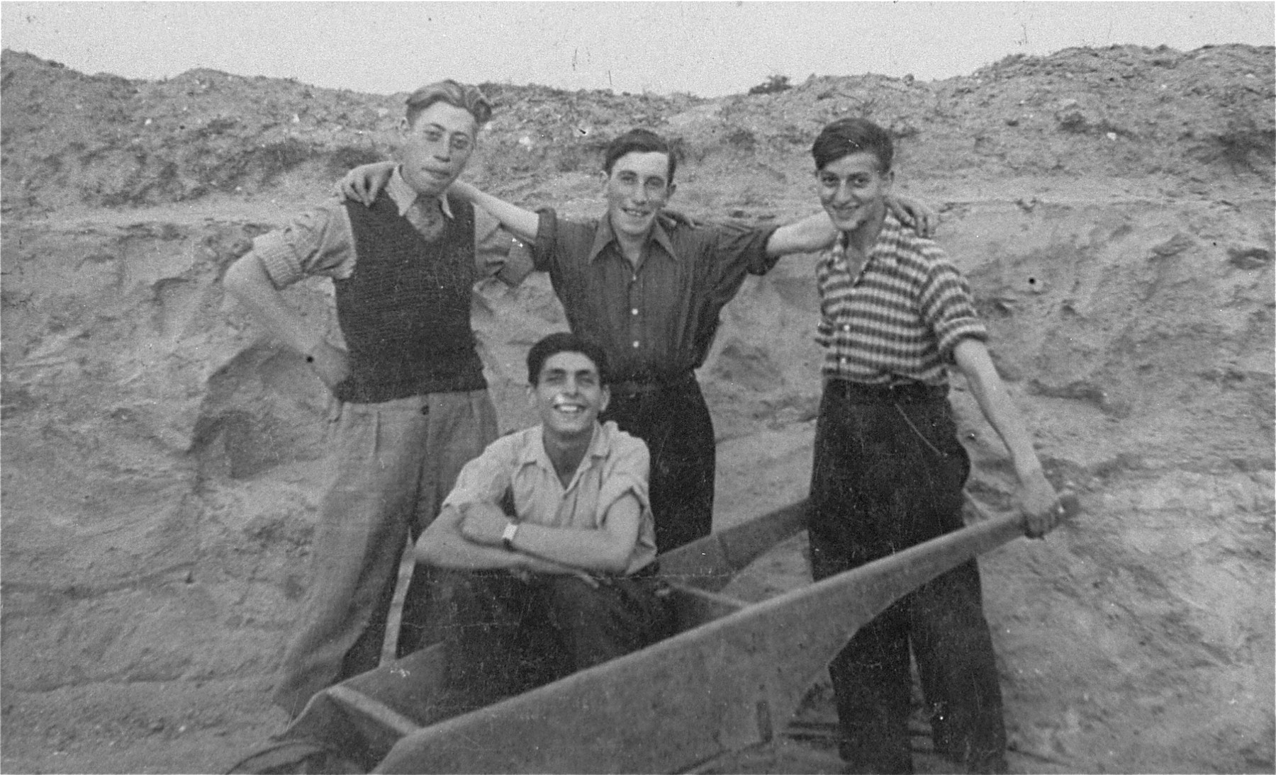 Four members of the Gordonia Zionist youth movement pose in a field in the Marysin quarter of the Lodz ghetto.   Pictured standing from left to right are: Israel Weinberg, Shlomo Flam and Ariel Schwartz; sitting in the wheelbarrow is Menachem Fogel (who later perished).