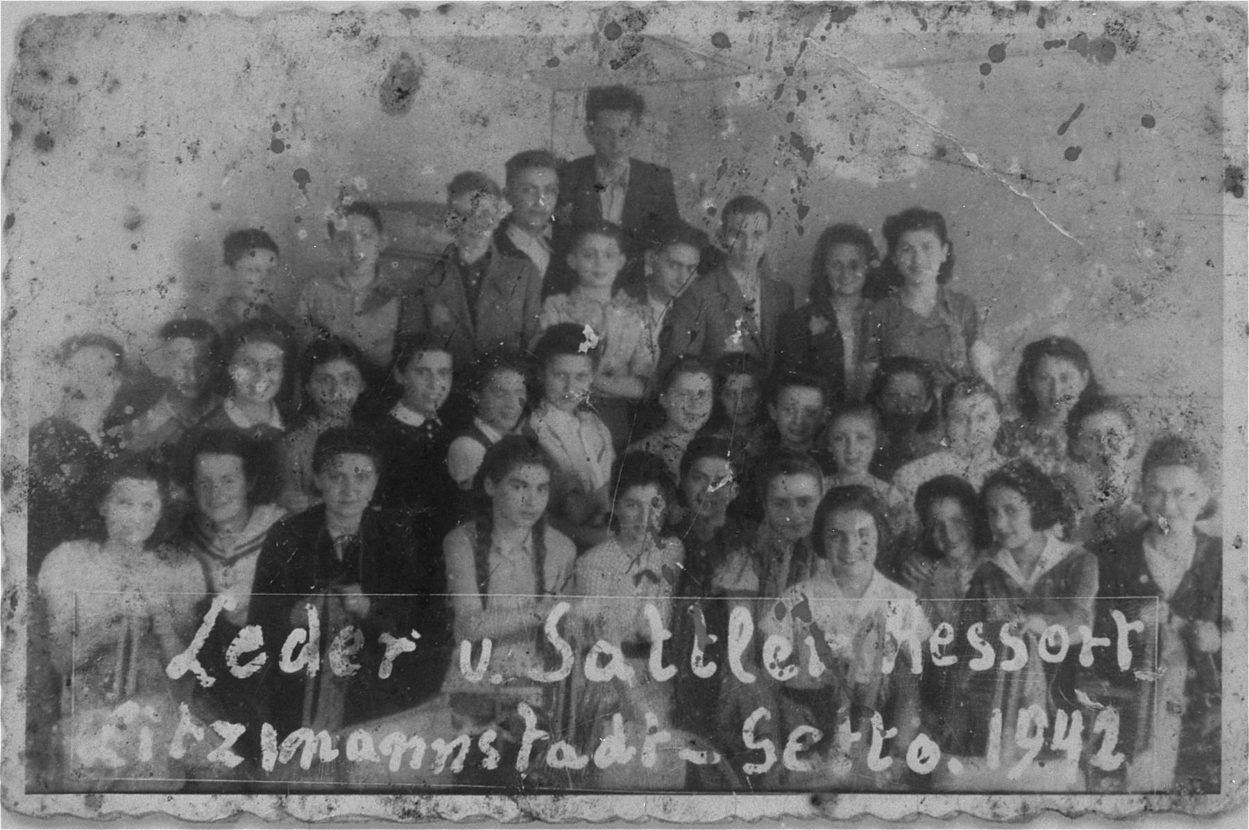 Group portrait of young forced laborers at the leather and saddle-making workshop in the Lodz ghetto.  Jakob Budkowski is pictured second row from the bottom, second from the left.