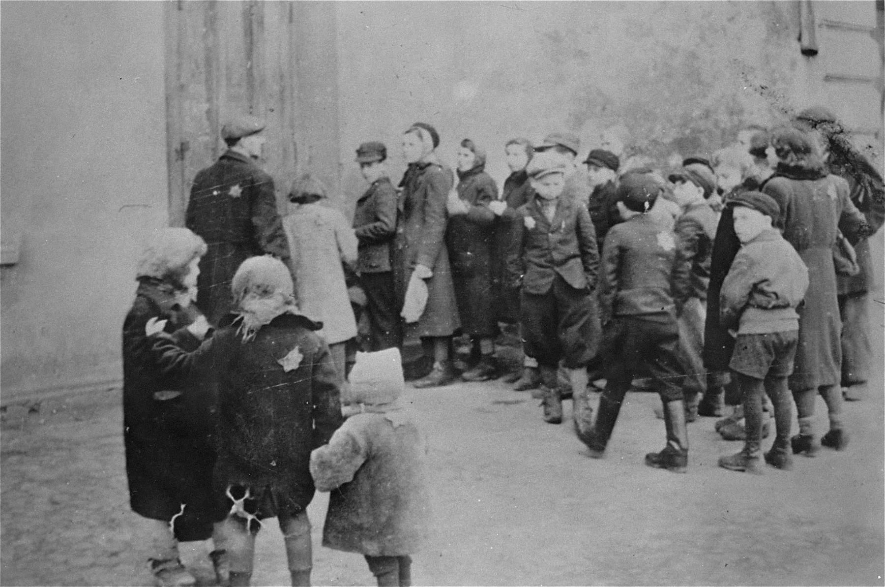 Lodz ghetto children waiting in line in front of a soup kitchen.