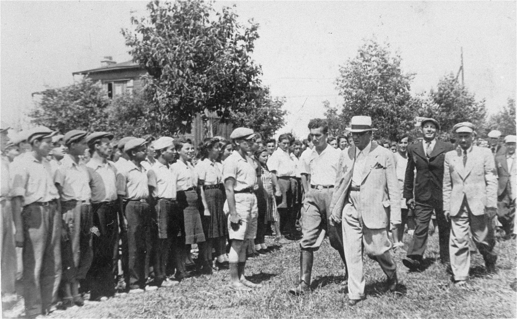 Mordechai Chaim Rumkowski, head of the Lodz ghetto Jewish council, and Leon Rosenblat, head of the Jewish police, review a group of Jewish youth during an official visit to the summer camp in the Marysin quarter of the Lodz ghetto.  Among the children pictured is Jakob Budkowski.  He was the son of Majer Szymon  Budkowski and  Szajna Zlata Lesz and was born May 13, 1927 in Lodz. He had three younger brothers; of his family, only Jakob survived.