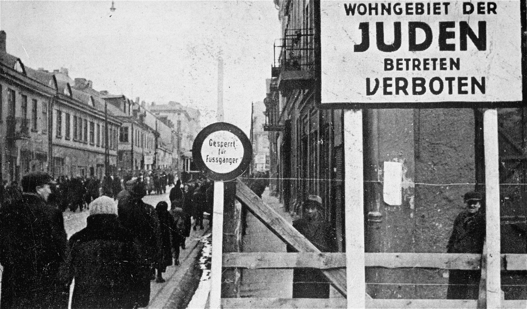 Postcard from the Lodz ghetto showing the entrance and a sign forbidding entrance to non-Jews to the ghetto.