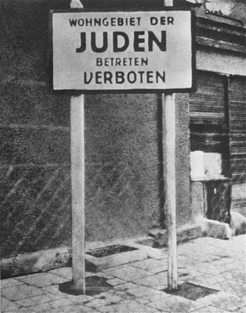 """An entrance into the Lodz ghetto with a sign that reads:  """"Jewish residential district: Entrance Forbidden."""""""