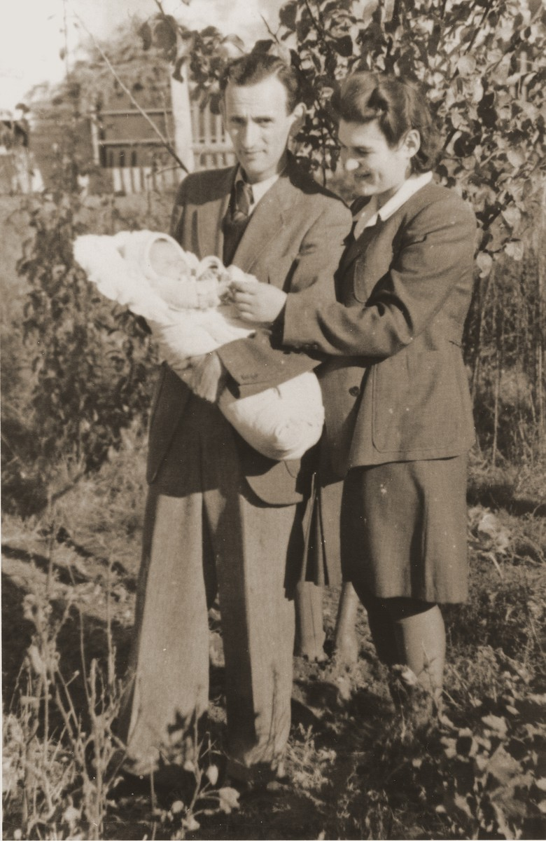 A young Jewish DP couple pose outside with their newborn daughter in the Fuerth displaced persons camp.    Pictured are Henryk and Eugenia (Hochberg) Lanceter with their infant, Dina.