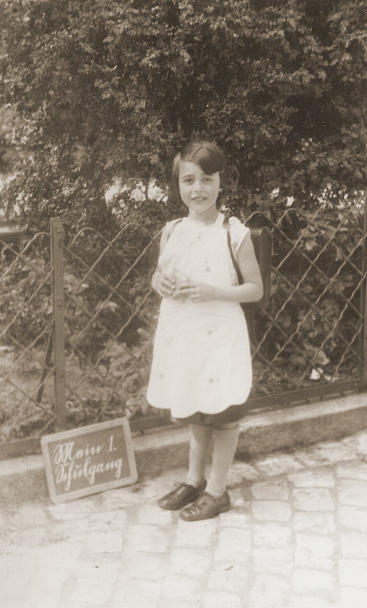 "Edith Loeb poses next to a slate that reads ""My first day of school."""