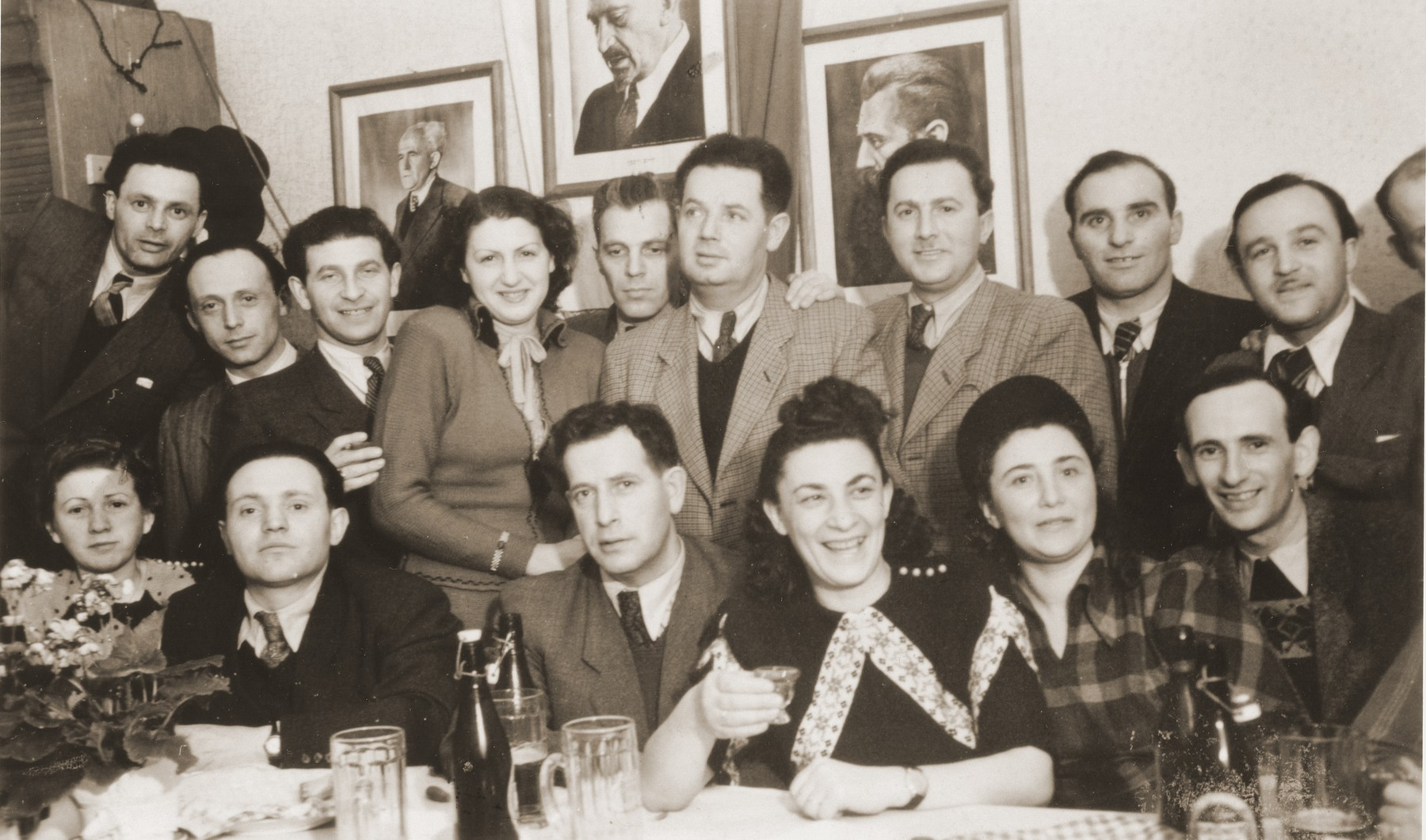 Group portrait of the members of the Betar Zionist youth movement gathered around a table in Fuerth, Germany.  Among those pictured are Manfred Schulman, Henek Schwartzbard, and Henryk Lanceter.