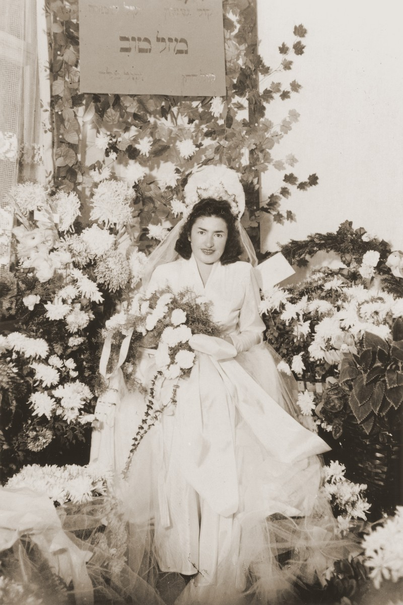 A Jewish DP bride sits on a throne surrounded by flowers in Fuerth, Germany.  Pictured is Sala (Rafilowicz) Springer, originally from Bedzin, Poland.   The wedding took place in the apartment of Gerda and Kuba Lebzetter.