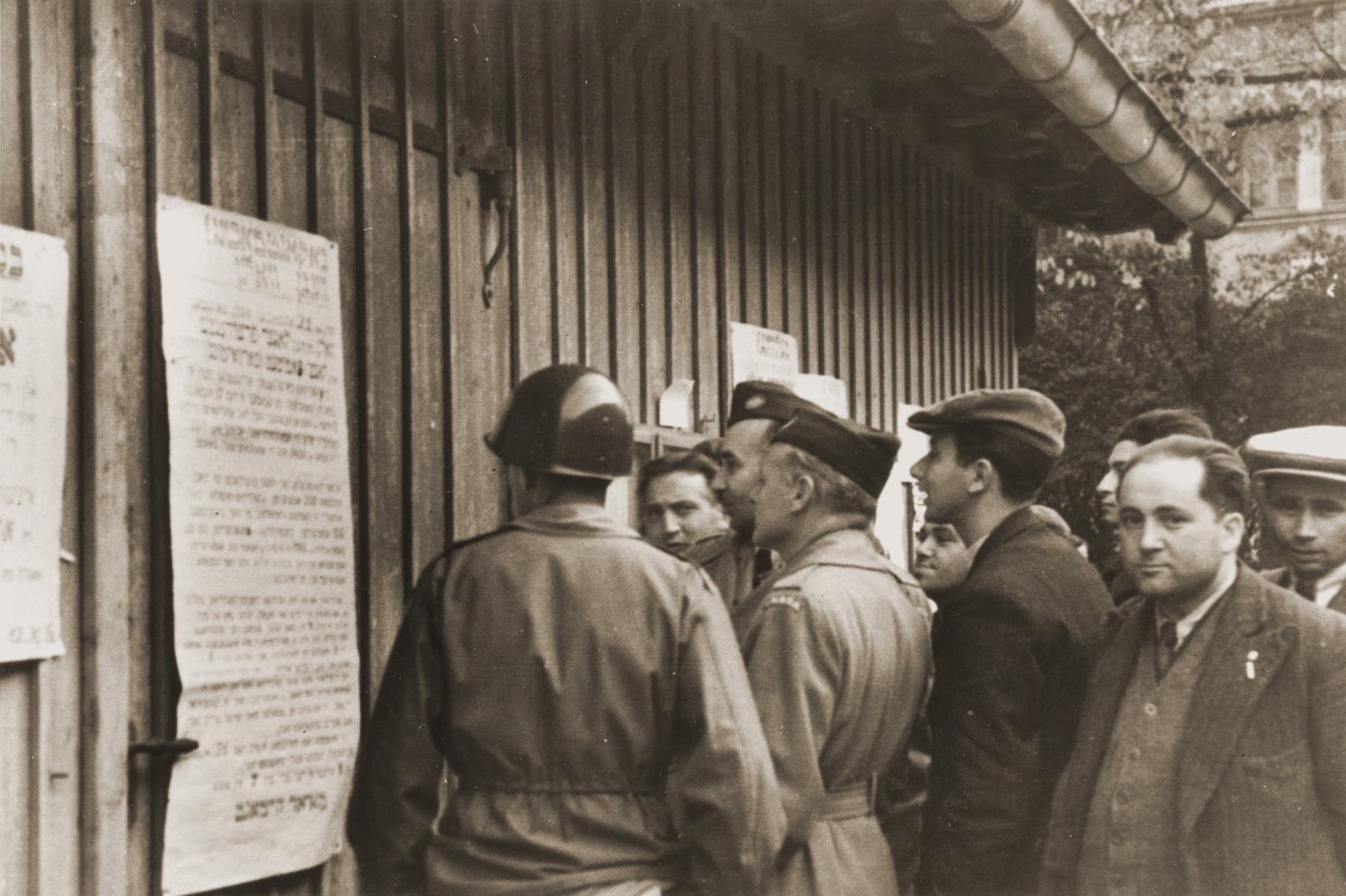 American officials read an election announcement posted outside the camp administration barracks in the Landsberg displaced persons camp.  Pictured from left to right are: Major Irving Heymont, camp director, Leo Srole, an UNRRA social worker who is translating the poster, and Dr. Abraham Glassgold, UNRRA director and a member of the camp committee.