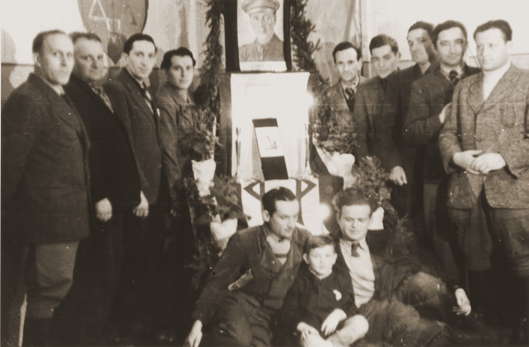 Group portrait of members of the Betar Zionist youth group in Fuerth alongside a portrait of Joseph Trumpeldor.  Among those pictured are Max Schatz, Leon Kreminitzer, Henryk Lanceter, and Jono Margulies.