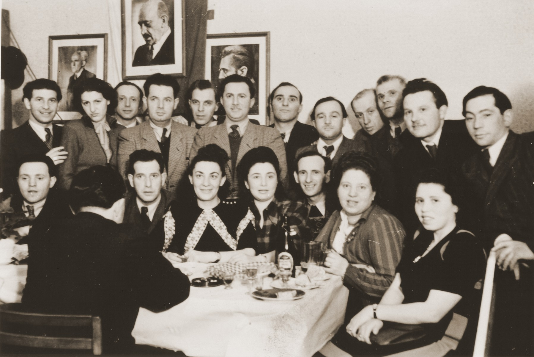 Group portrait of members of the Betar Zionist youth movement gathered around a table in Fuerth, Germany.  Among those pictured are Manfred Schulman, Henek Schwartzbard, Henryk Lanceter, and Klara Schwartzbard.