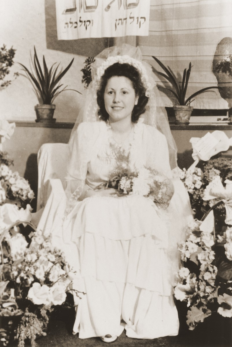 "A Jewish DP bride sits on a throne surrounded by flowers in Fuerth, Germany.  Pictured is Esther Rosenberg, originally from Ulanow.  Her groom is Tadek Blacharowicz from Kielce. Esther sits beneath a Hebrew sign that reads, ""Congratulations.  The voice of the groom, the voice of the bride."""