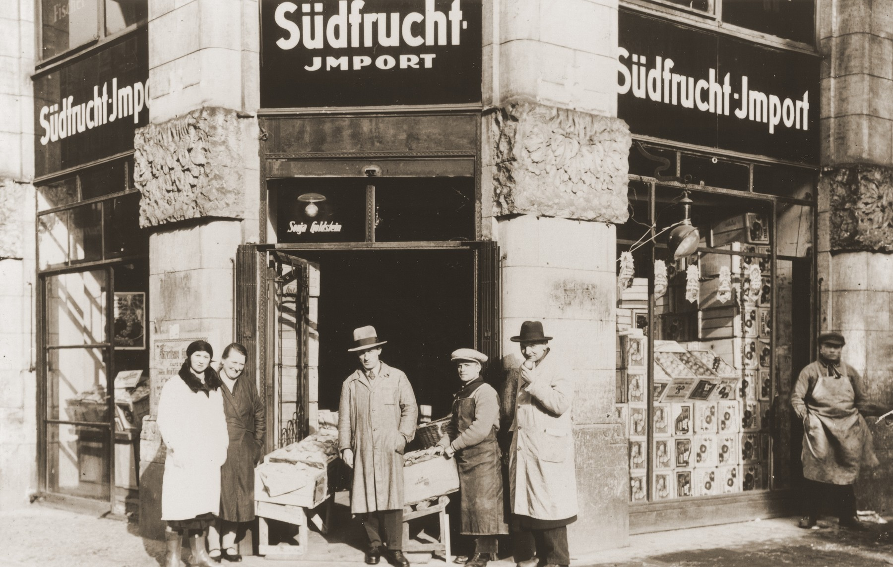 Bernhard and Sonja Schadur Goldstein with others in front of their wholesale fruit business in Berlin.  Bernhard is pictured in the center and Sonja, at the left.  Sonja was the sister of Michel Schadur, whom he set up in the fruit business in Berlin in the early 1930s.  Sonja married a German-Jew, Bernhard Goldstein and had one daughter while living in Berlin.  After Kristallnacht Bernhard was imprisoned briefly in Sachsenhausen.  Upon his release the family fled to Antwerp.  In March 1940 they secured American visas and sailed to the U.S.