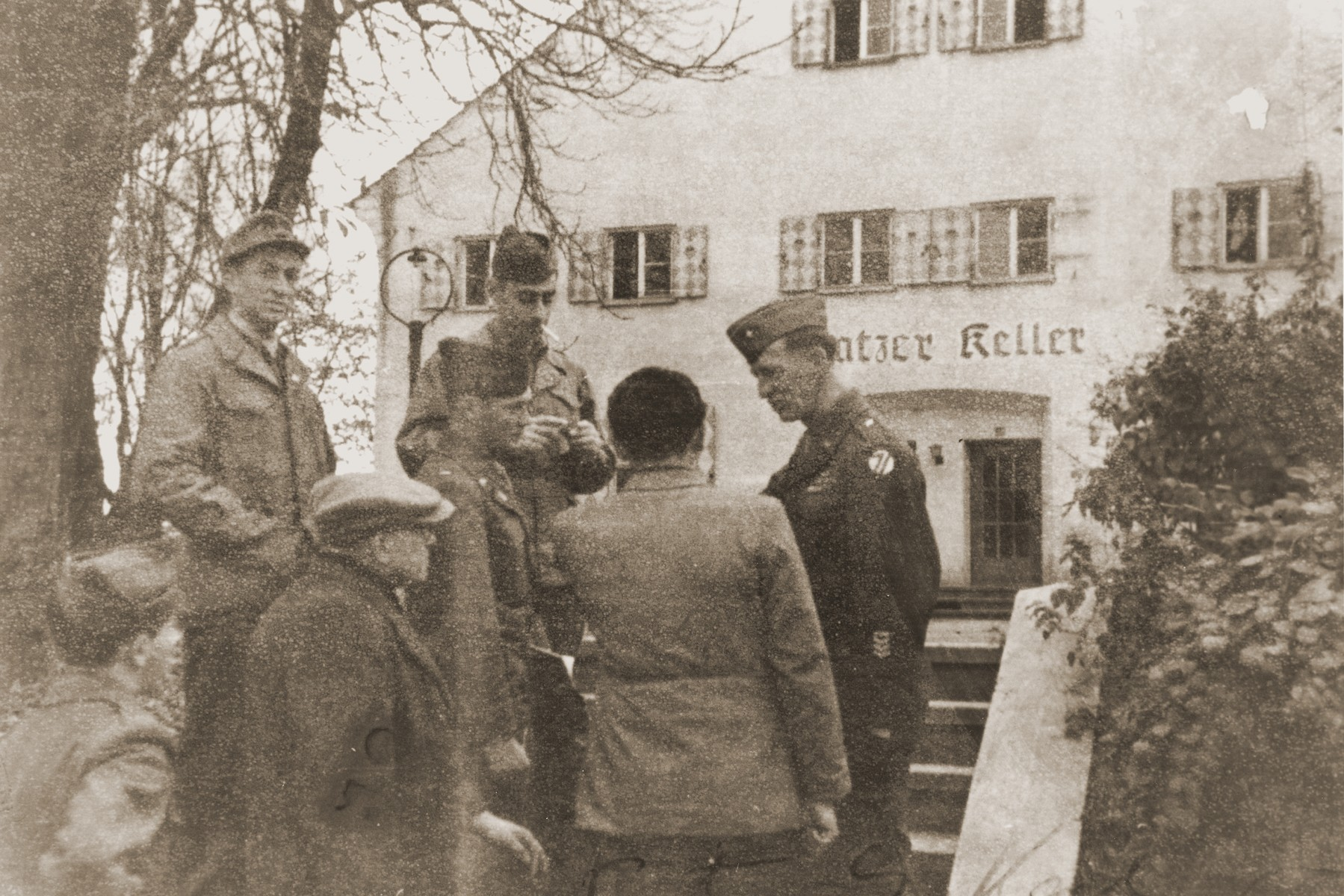 General Onslow Rolfe (top, right) and Major Irving Heymont (top, center) speak to Jewish DPs outside an administrative building in the Landsberg displaced persons camp.    Also pictured is Dr. Samuel Gringauz (at the lower left).