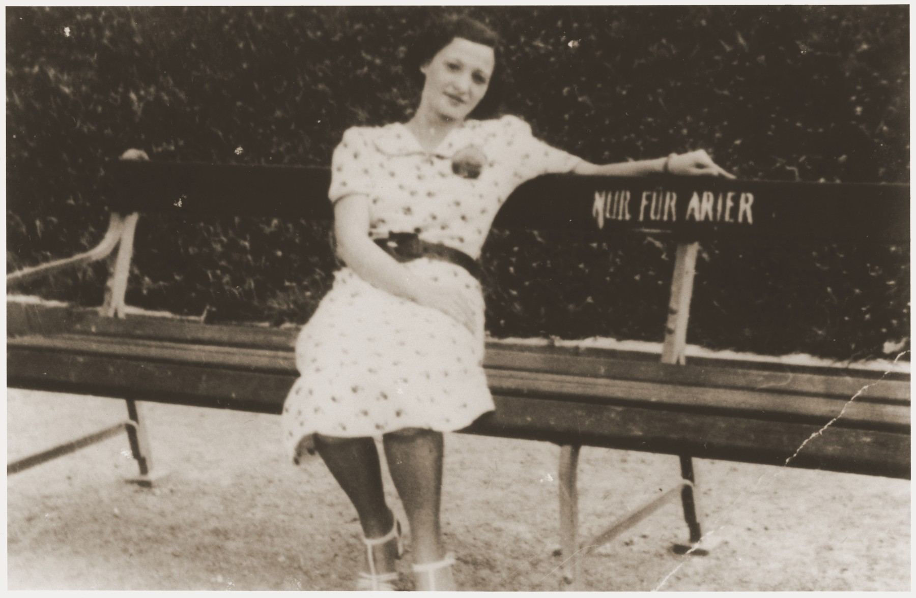 "Lizi Rosenfeld, a friend of the Spitzers, sits on a park bench with a sign ""Only for Aryans."""