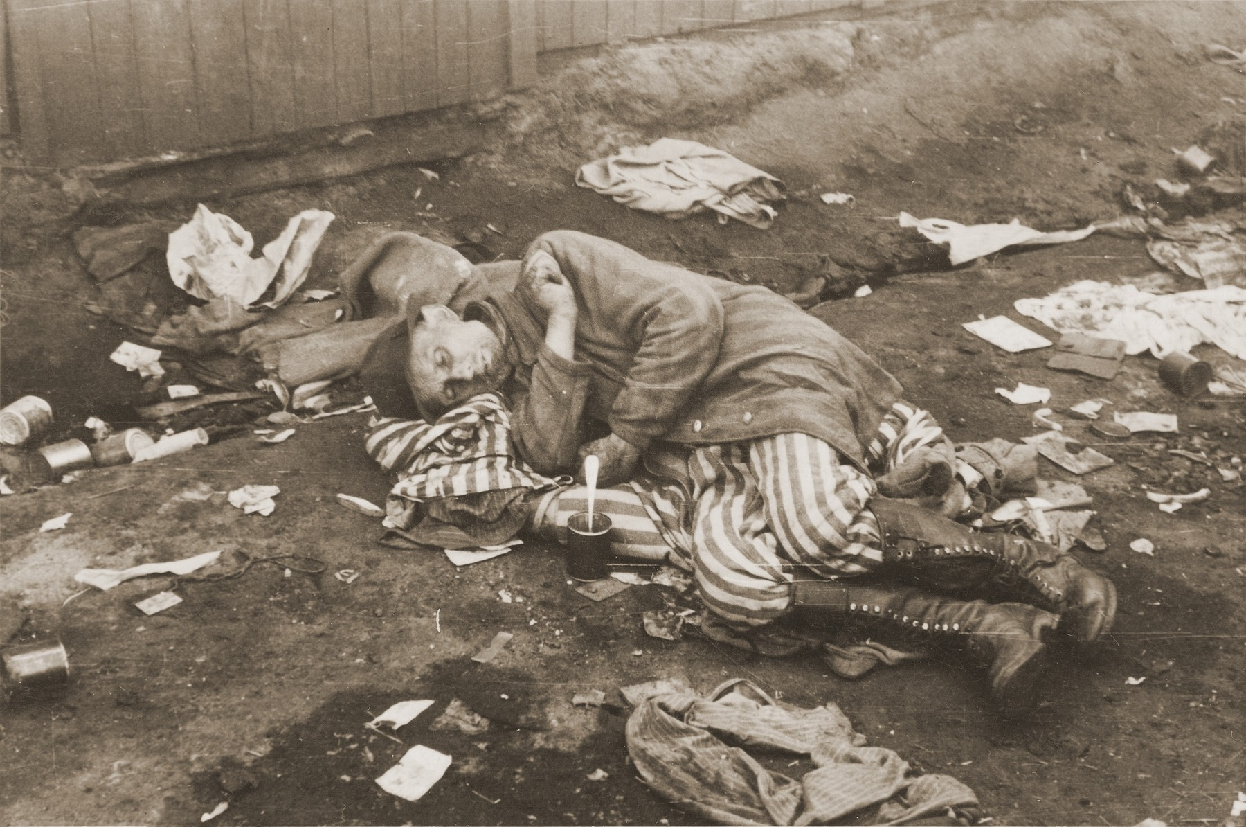 Having just eaten a tin of canned food given to him by British troops, and wearing a newly acquired pair of boots, a survivor in Bergen-Belsen sleeps on a pile of prisoners' uniforms.