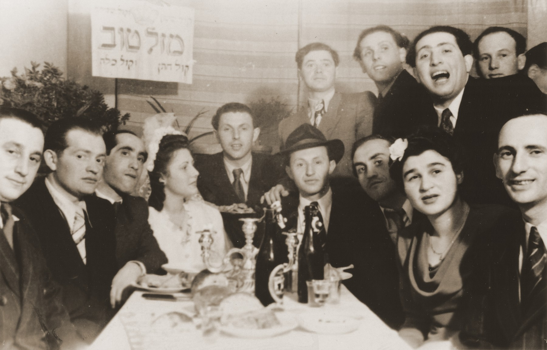 """Jewish DPs gather around a table to celebrate the wedding of Tadek Blacharowicz and Esther Rosenberg.  Pictured at the head of the table are the bride and the groom.  Also pictured are Henryk and Eugenia Lanceter (seated first and second on the right), Moishe Rafilowicz (third from the left), Szaje Rosenberg (between the bride and the groom) and Max Bocher (top row, second from the right).    The Hebrew sign at the top reads, """"Congratulations, the voice of the groom, the voice of the bride."""