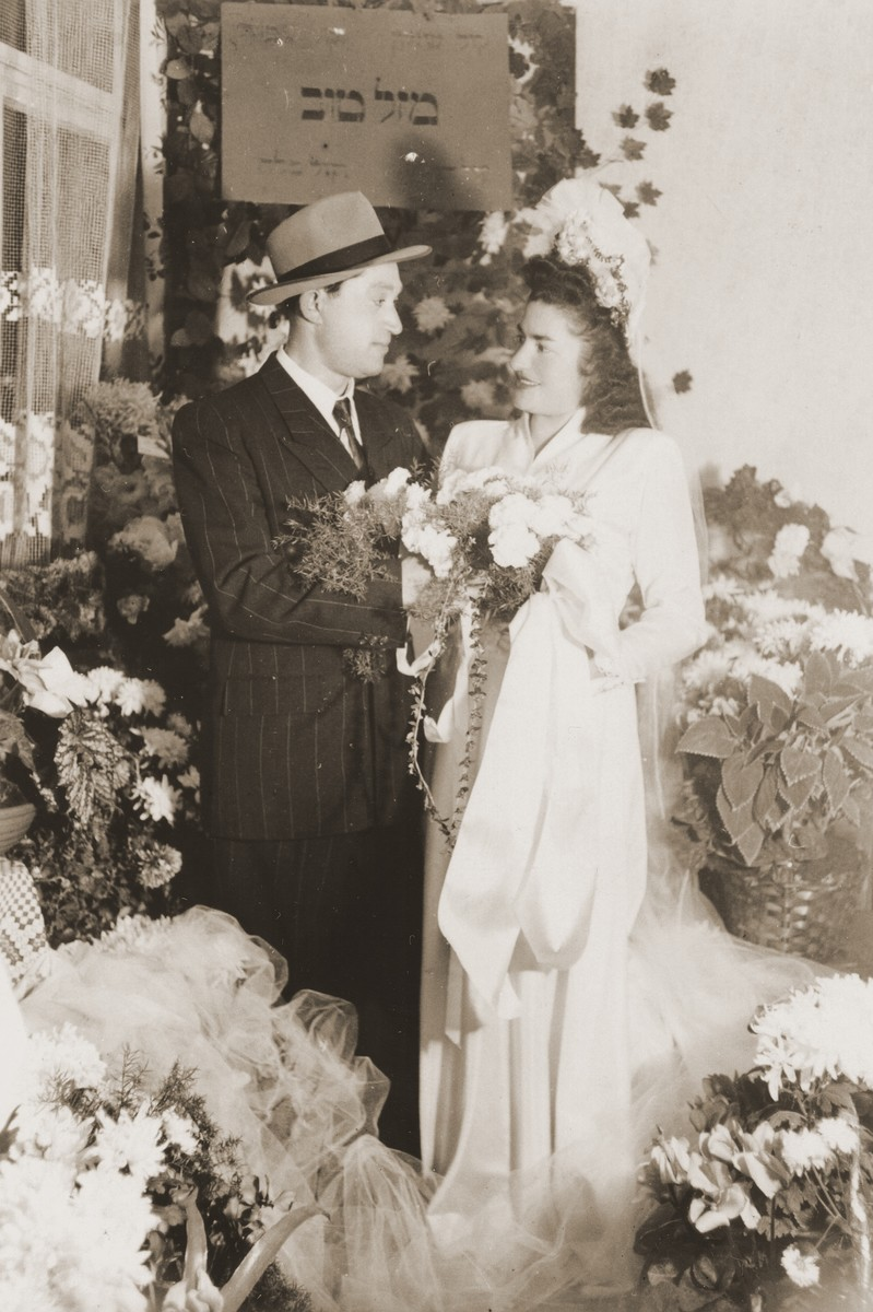 """Wedding portrait of a Jewish DP couple in Fuerth, Germany.  Pictured are I. Rafilowicz (groom) and Sala Springer (bride).  The couple poses beneath a Hebrew sign that reads, """"Congratulations.""""  The wedding took place in the apartment of Gerda and Kuba Lebzetter. t"""