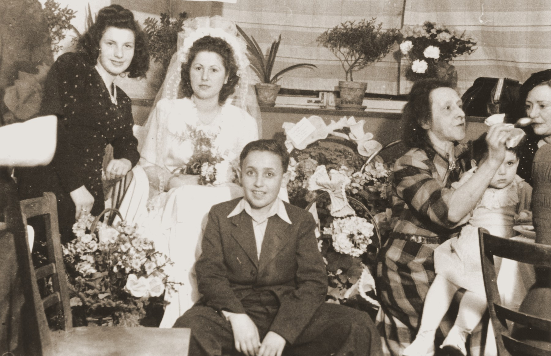 A Jewish DP bride sits among friends during her wedding celebration in Fuerth, Germany.  Among those pictured is the bride, Esther Rosenberg, Hirsch Langburt (kneeling), and the little girl, Dina Lanceter (right).