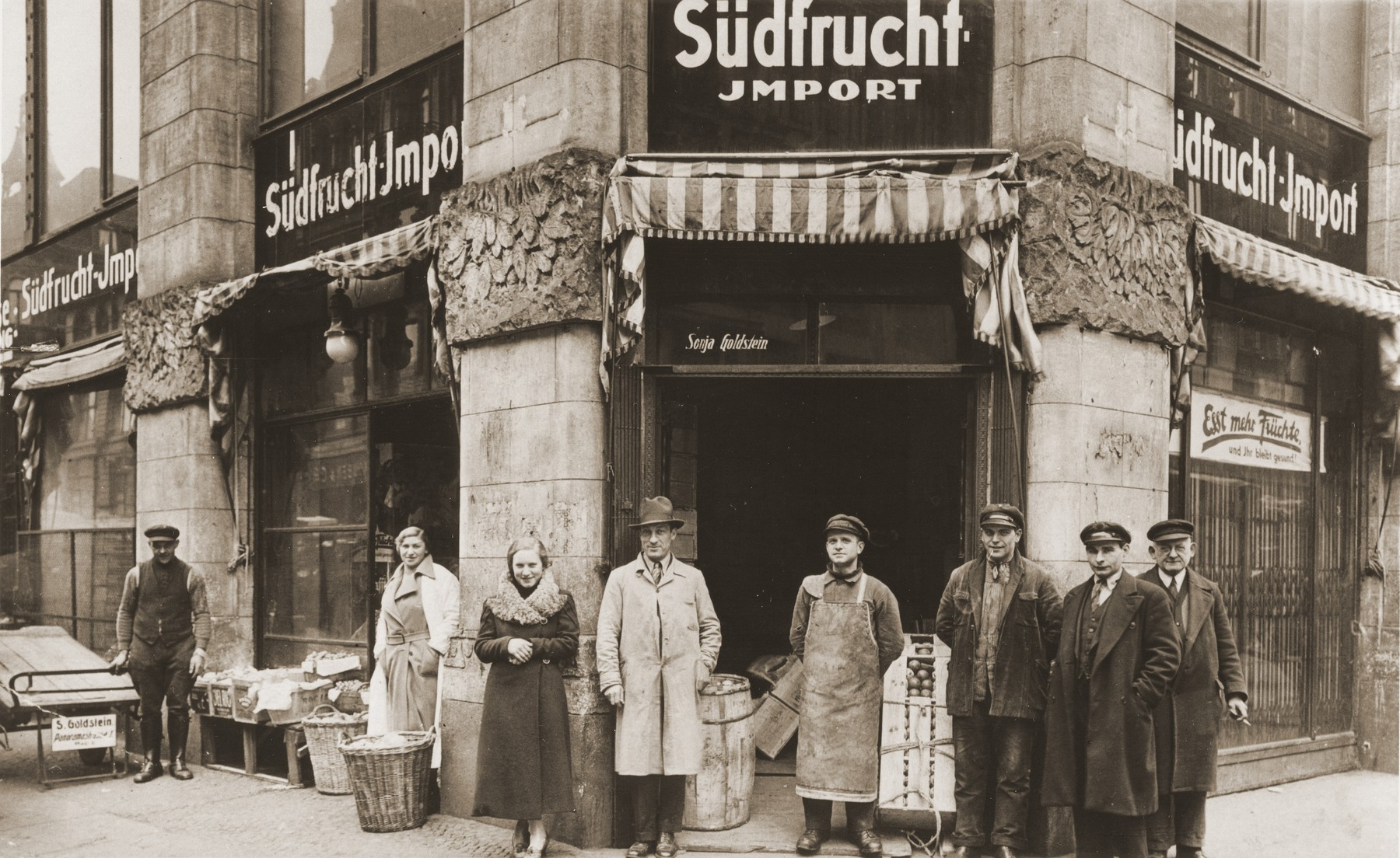Bernhard and Sonja Schadur Goldstein pose with some of their employees in front of their fruit business in Berlin.  Sonja is pictured on the left behind a basket.  Bernhard is in the center wearing a trench coat.  Sonja was the sister of Michel Schadur, whom he set up in the fruit business in Berlin in the early 1930s.  Sonja married a German-Jew, Bernhard Goldstein and had one daughter while living in Berlin.  After Kristallnacht Bernhard was imprisoned briefly in Sachsenhausen.  Upon his release the family fled to Antwerp.  In March 1940 they secured American visas and sailed to the U.S.