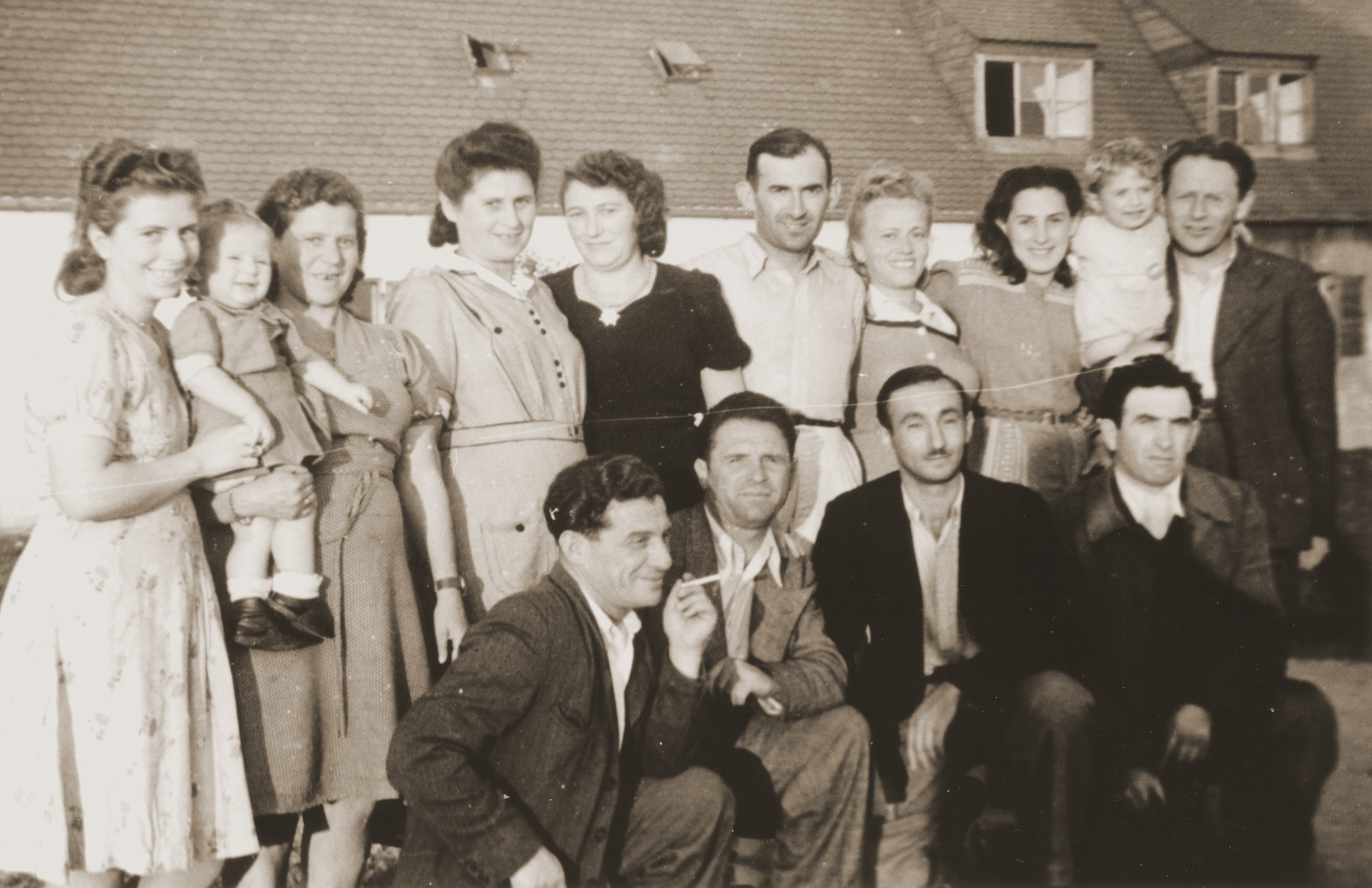 Group portrait of Jewish DP survivors from Brody, Poland at a reunion in the Foehrenwald displaced persons camp on the first day of the Jewish holiday of Sukkoth, 1946.  Among those pictured are Greta (Gruenfeld) Chalfin, Lisa Chalfin, Herman Rosenfeld, Genya Rosenfeld, Rachel Katz, and Szmulik Katz.