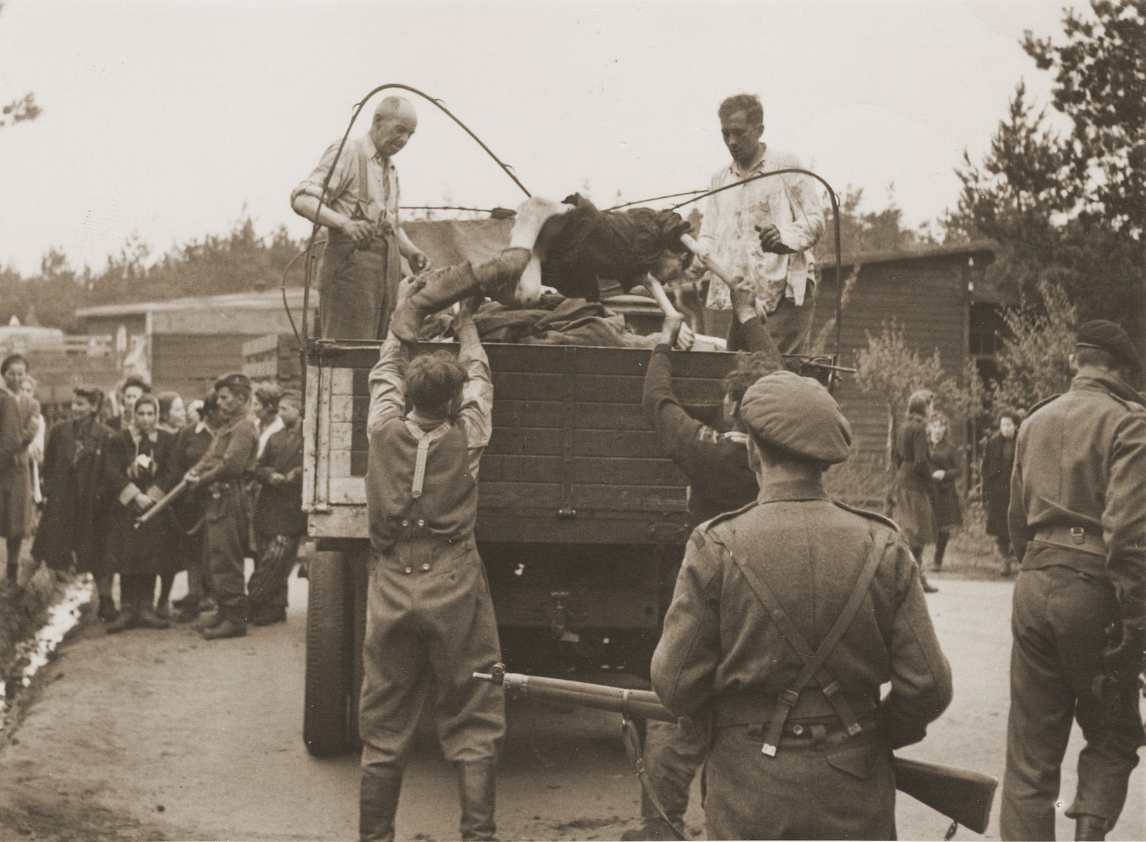 Captured SS guards, under British guard, load the corpses of prisoners who died in Bergen-Belsen concentration camp.